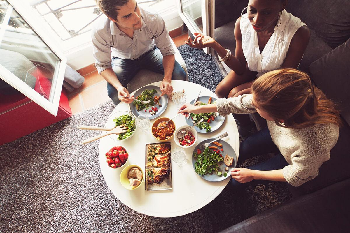 a group of people sitting at a table with a plate of food