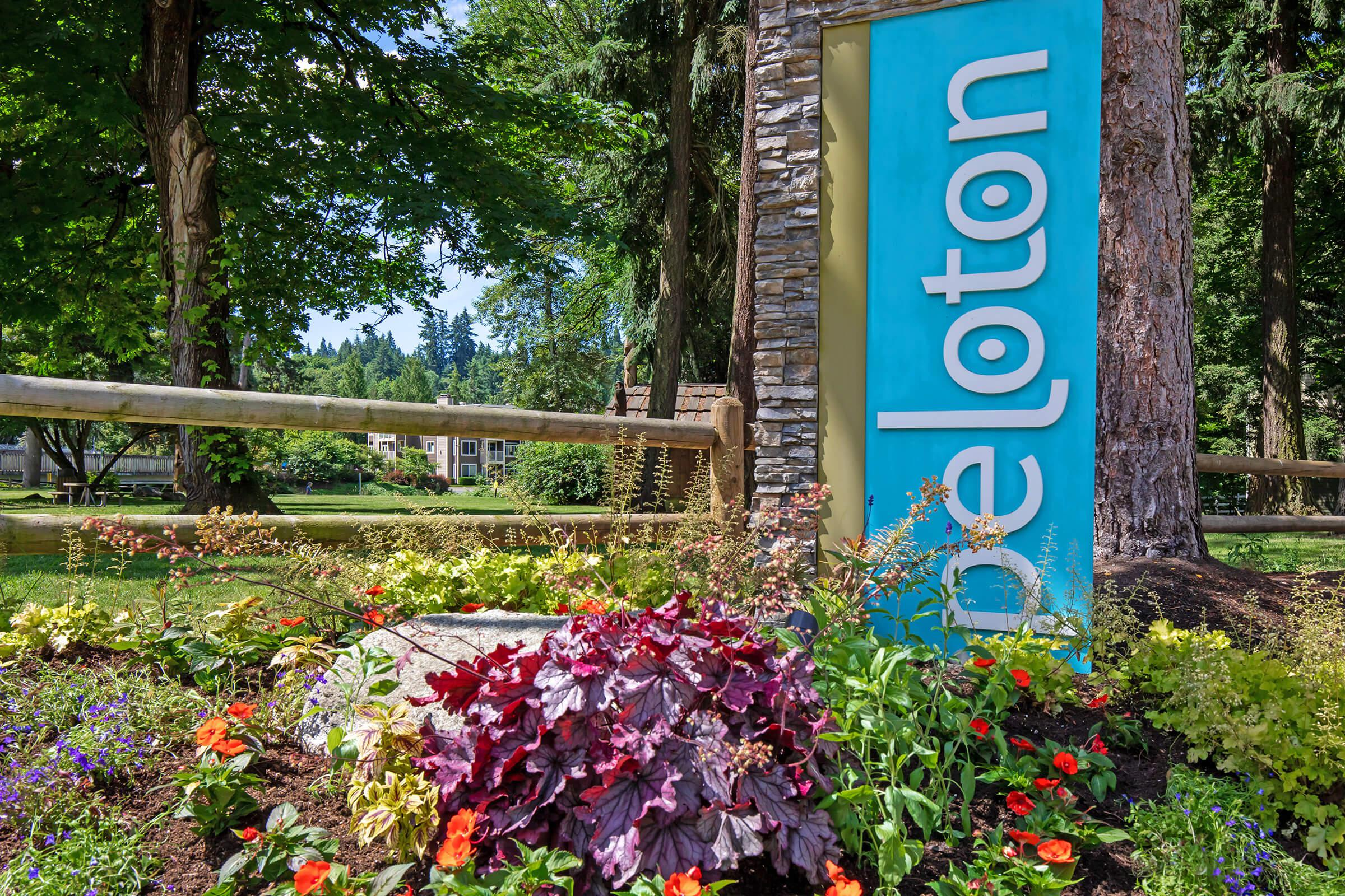 a sign in front of a flower garden