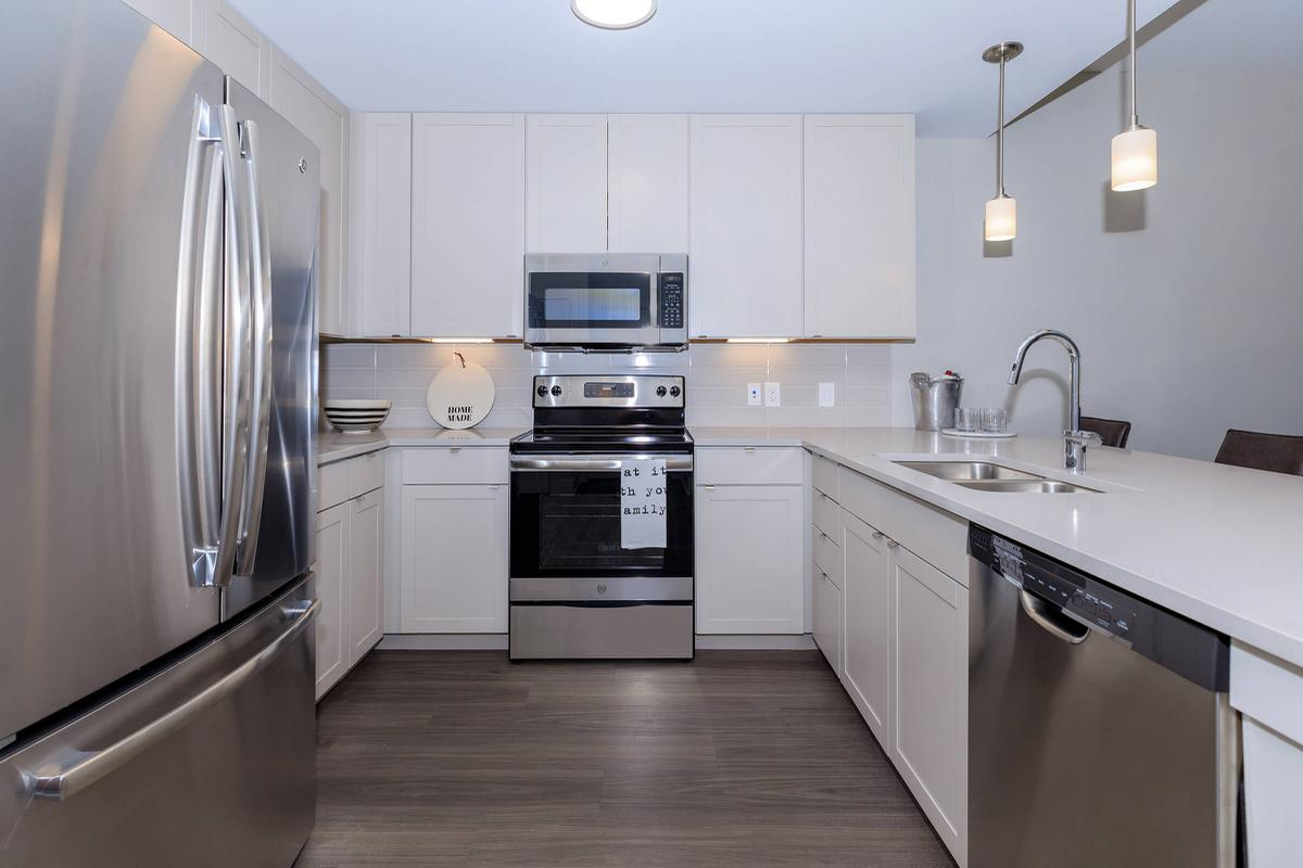a kitchen with white cabinets and stainless steel appliances