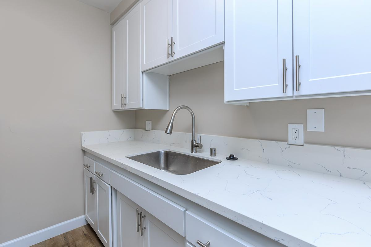a kitchen with white cabinets and a sink