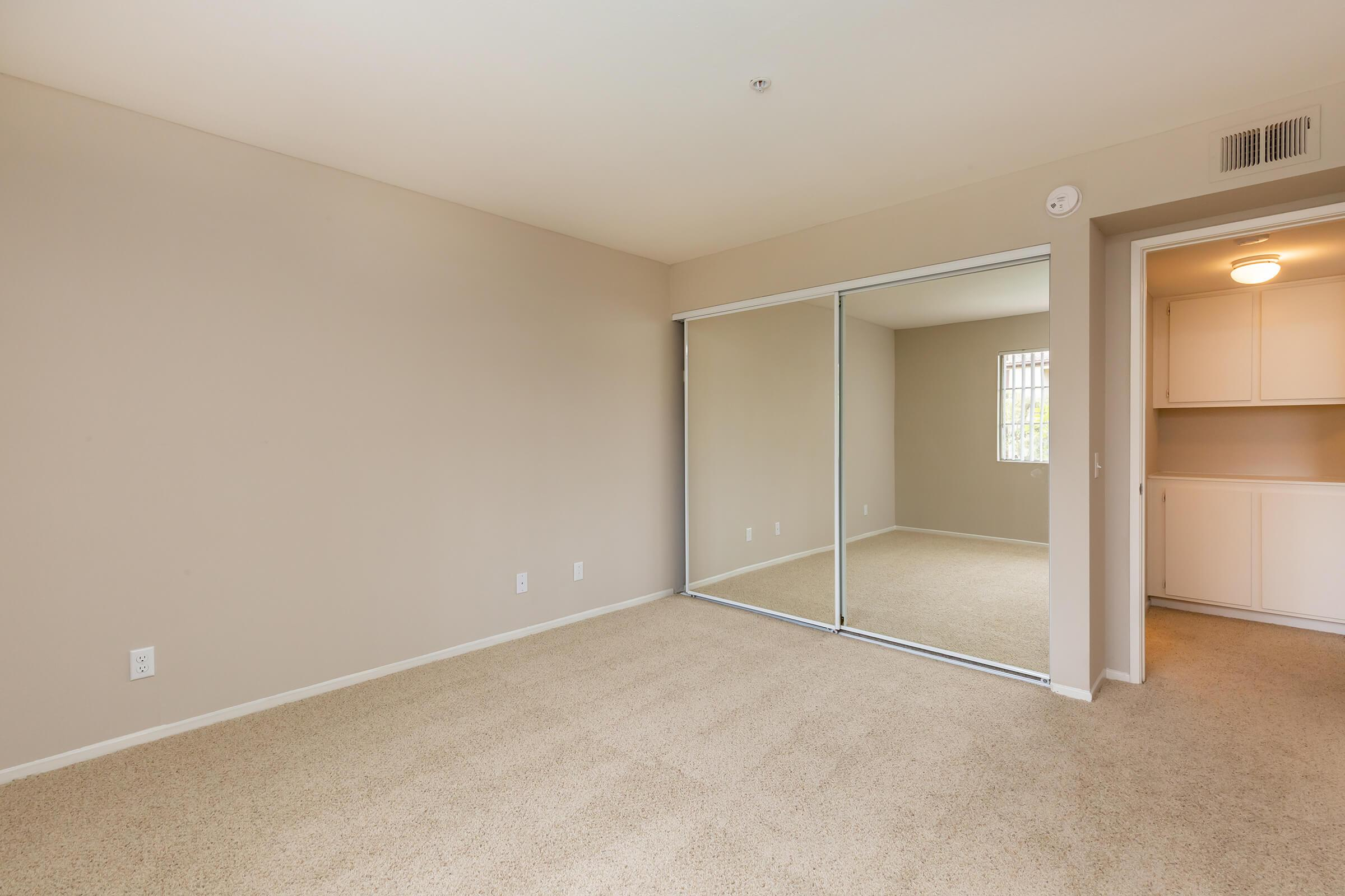 Carpeted bedroom with sliding mirror glass closet doors