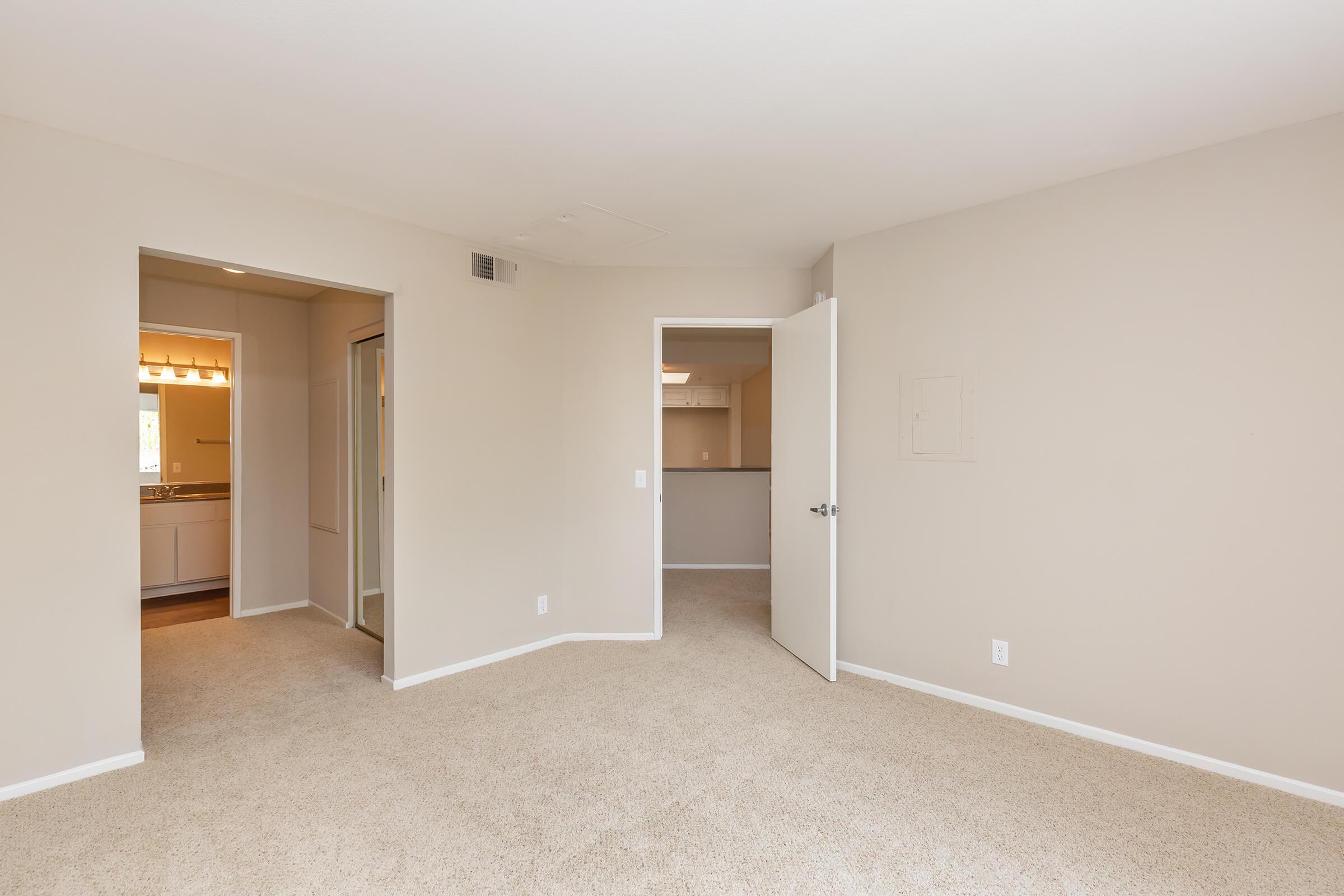 Unfurnished carpeted bedroom with open closet and bathroom doors