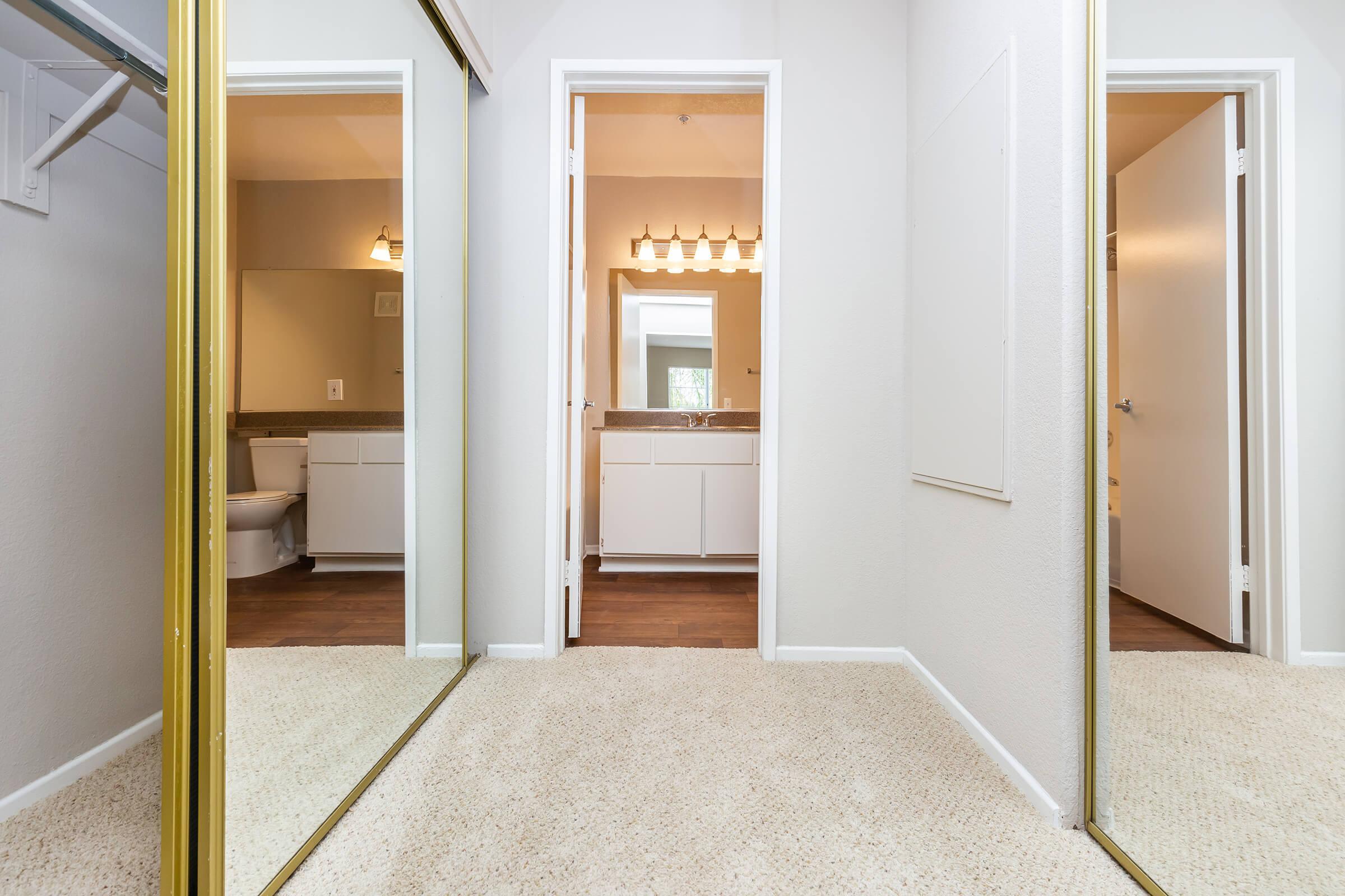 Two sets of sliding mirror glass closets doors with open bathroom door