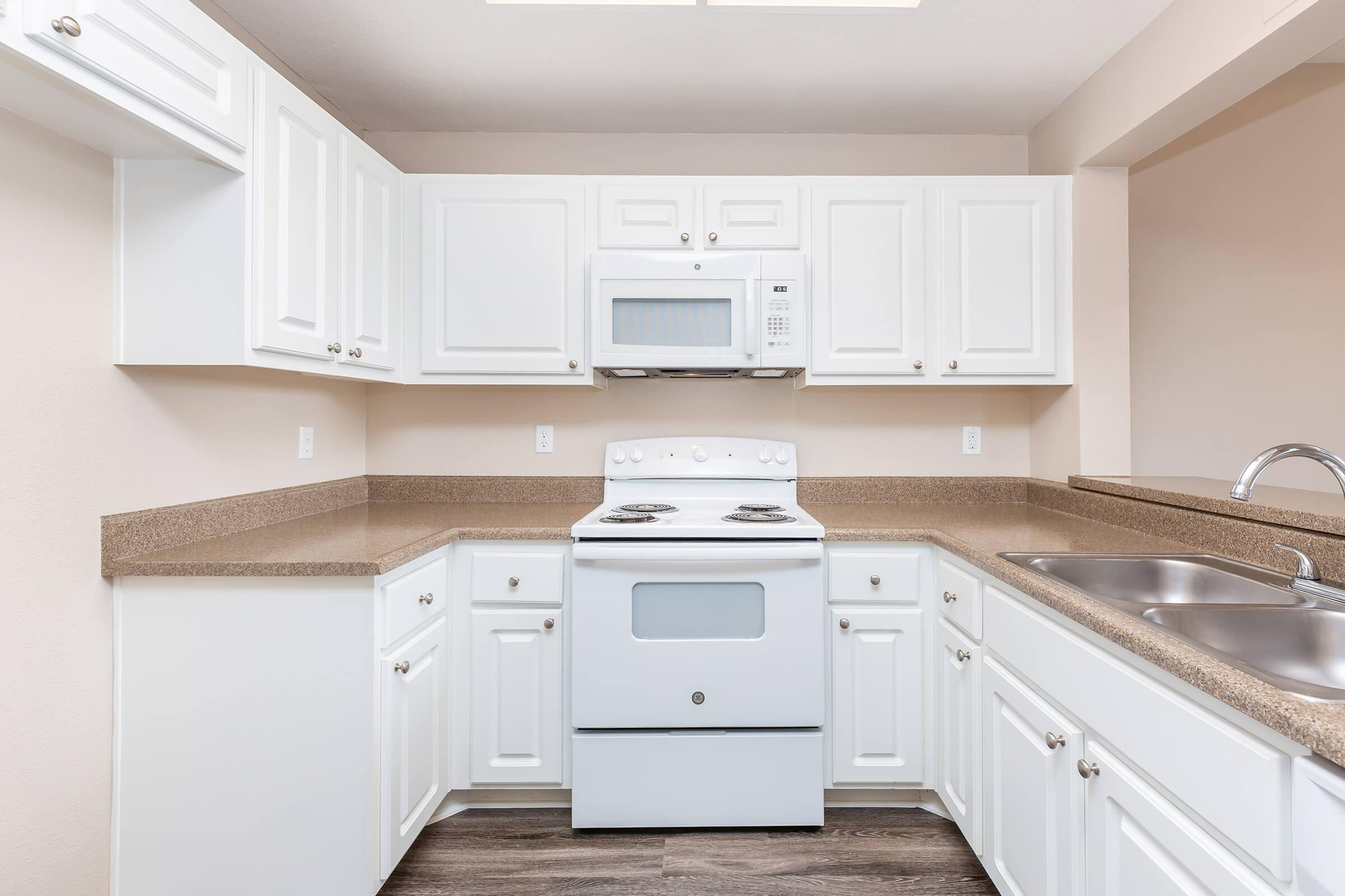 Vacant kitchen with white appliances
