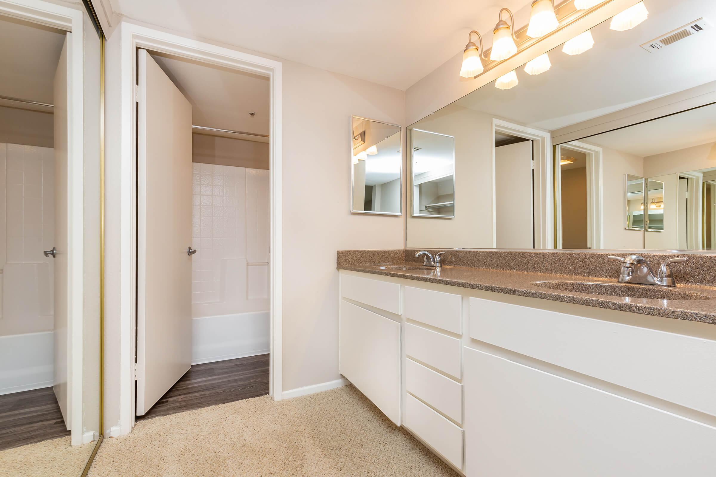 Two bathroom sinks across from a sliding mirror glass closet door