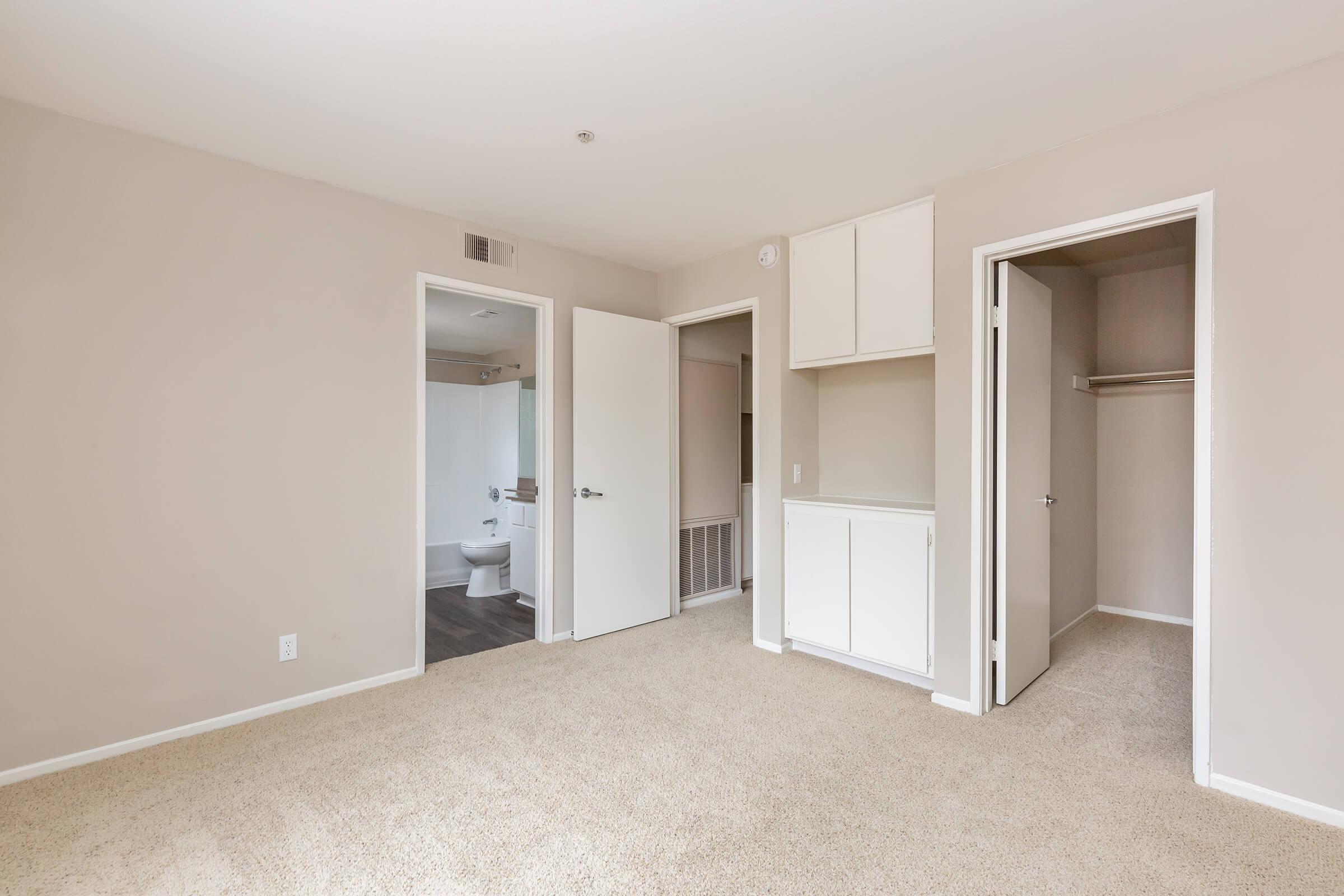 Vacant bedroom with open walk-in closet and bathroom doors