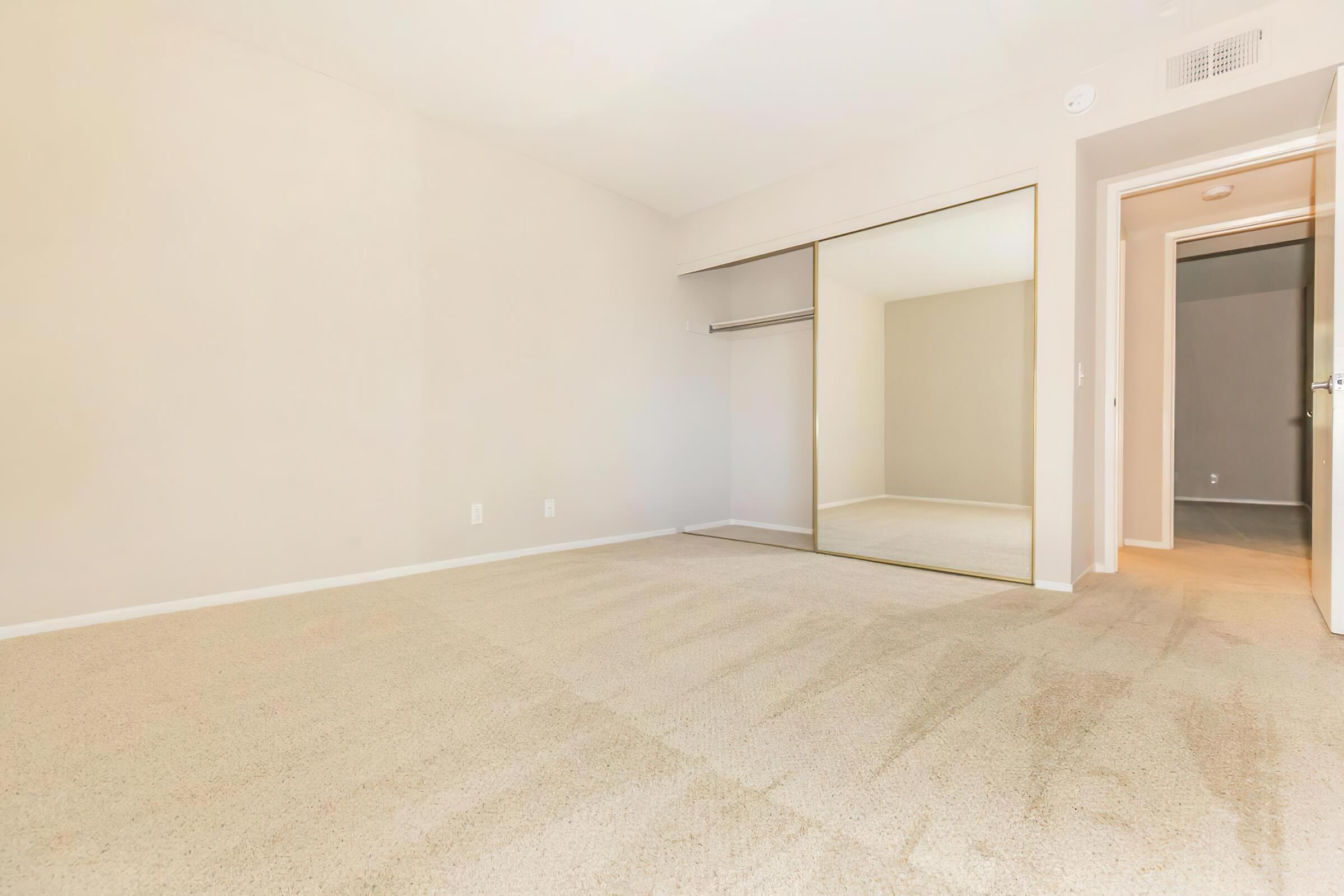Vacant bedroom with open sliding mirror glass closet door
