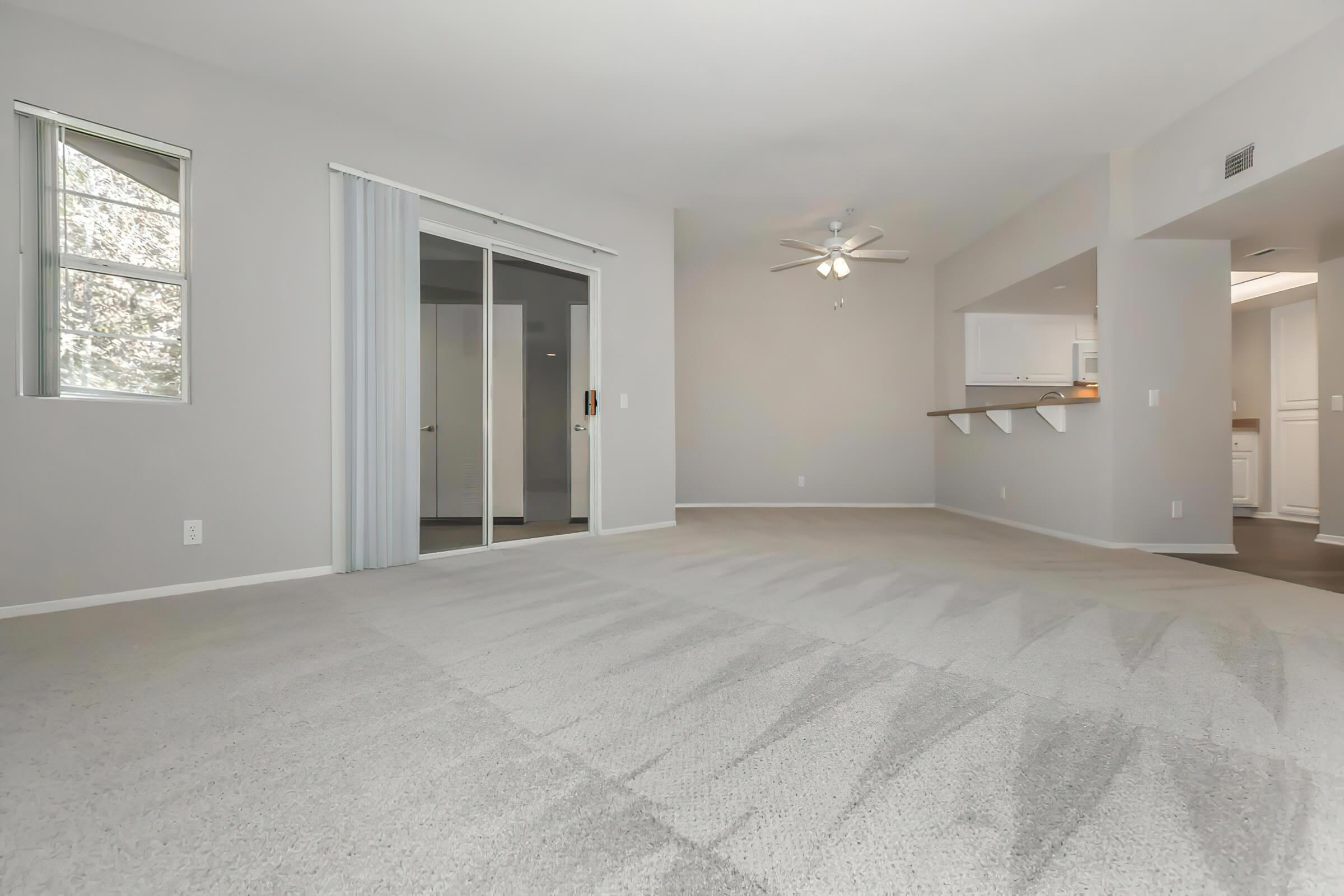 Vacant living room with carpet and sliding glass doors