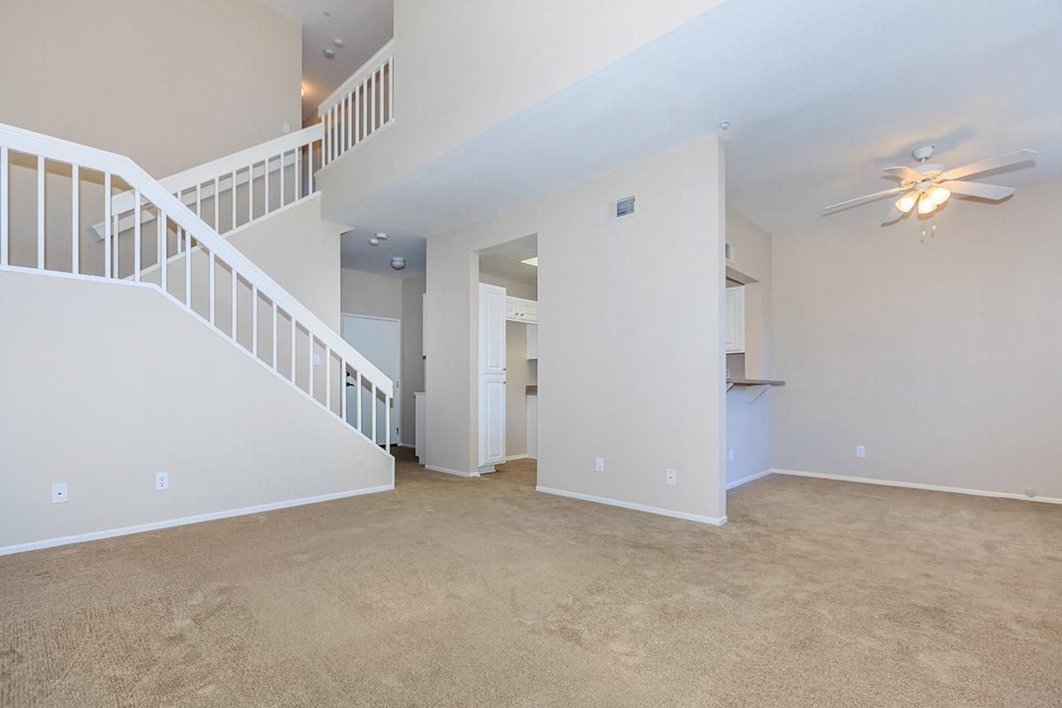 Carpeted living room with stairs