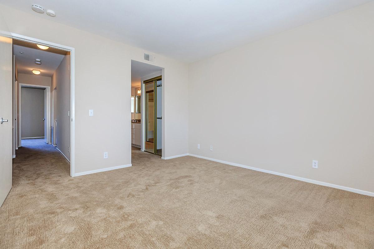 Vacant bedroom with open sliding closet doors