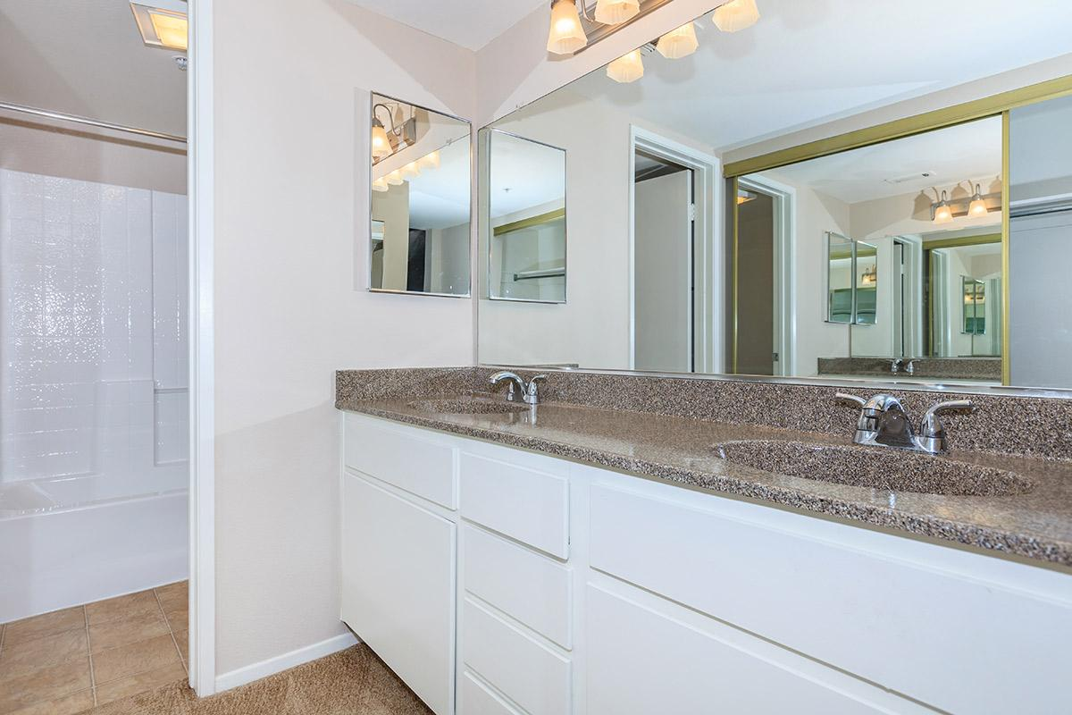 Two bathroom sinks with white cabinets