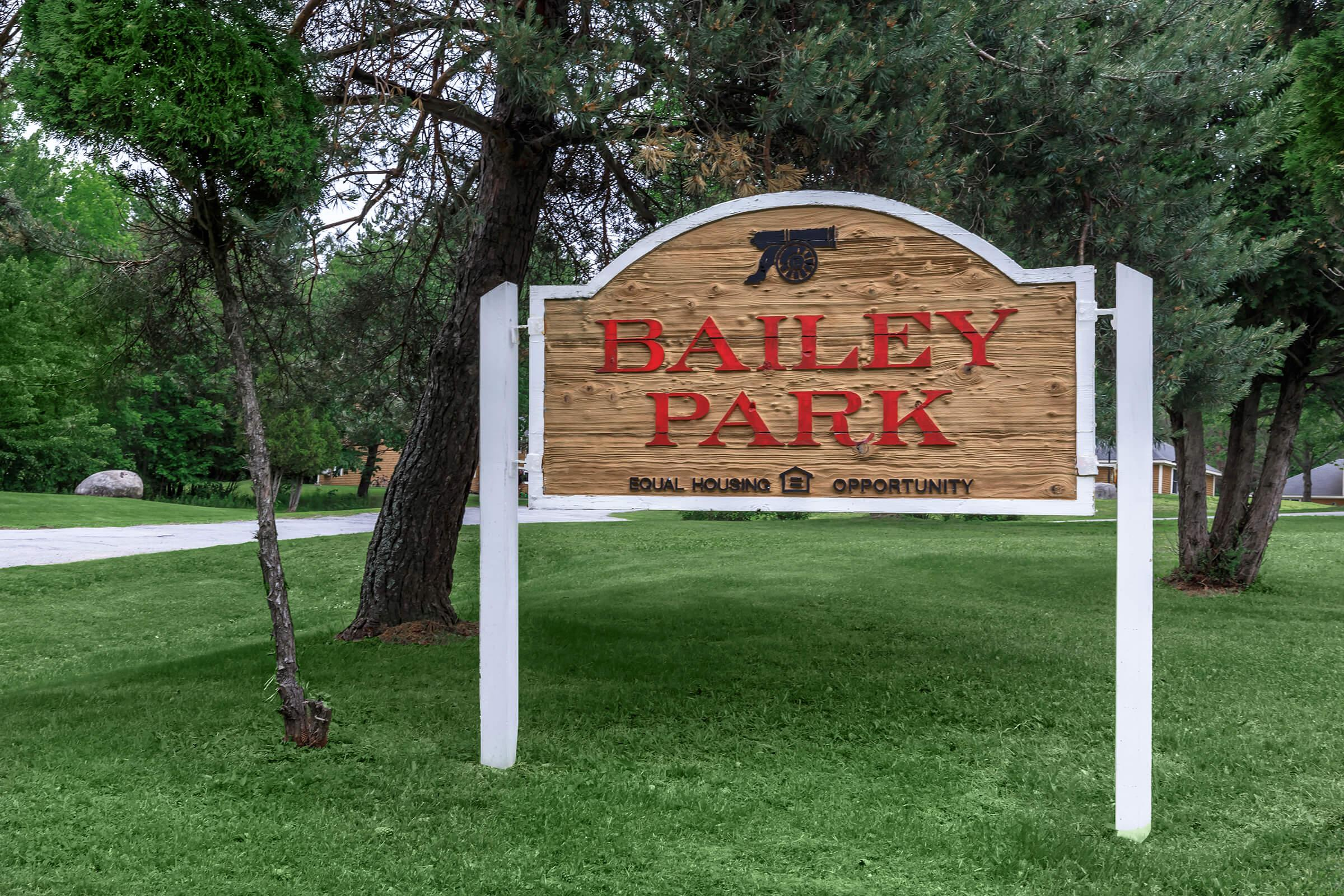a sign over a grassy area with trees in the background