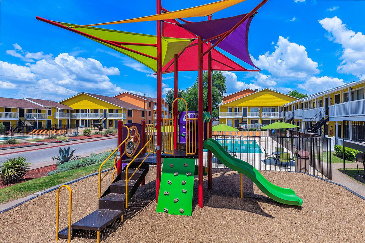 a playground with a green umbrella