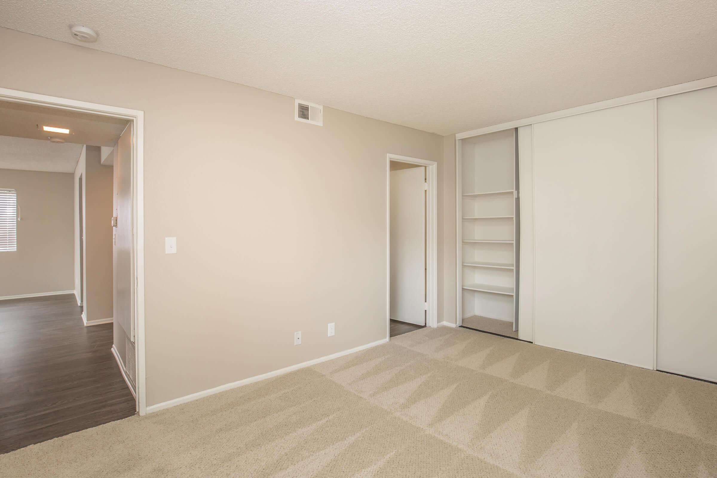 Unfurnished bedroom with open bathroom and closet doors