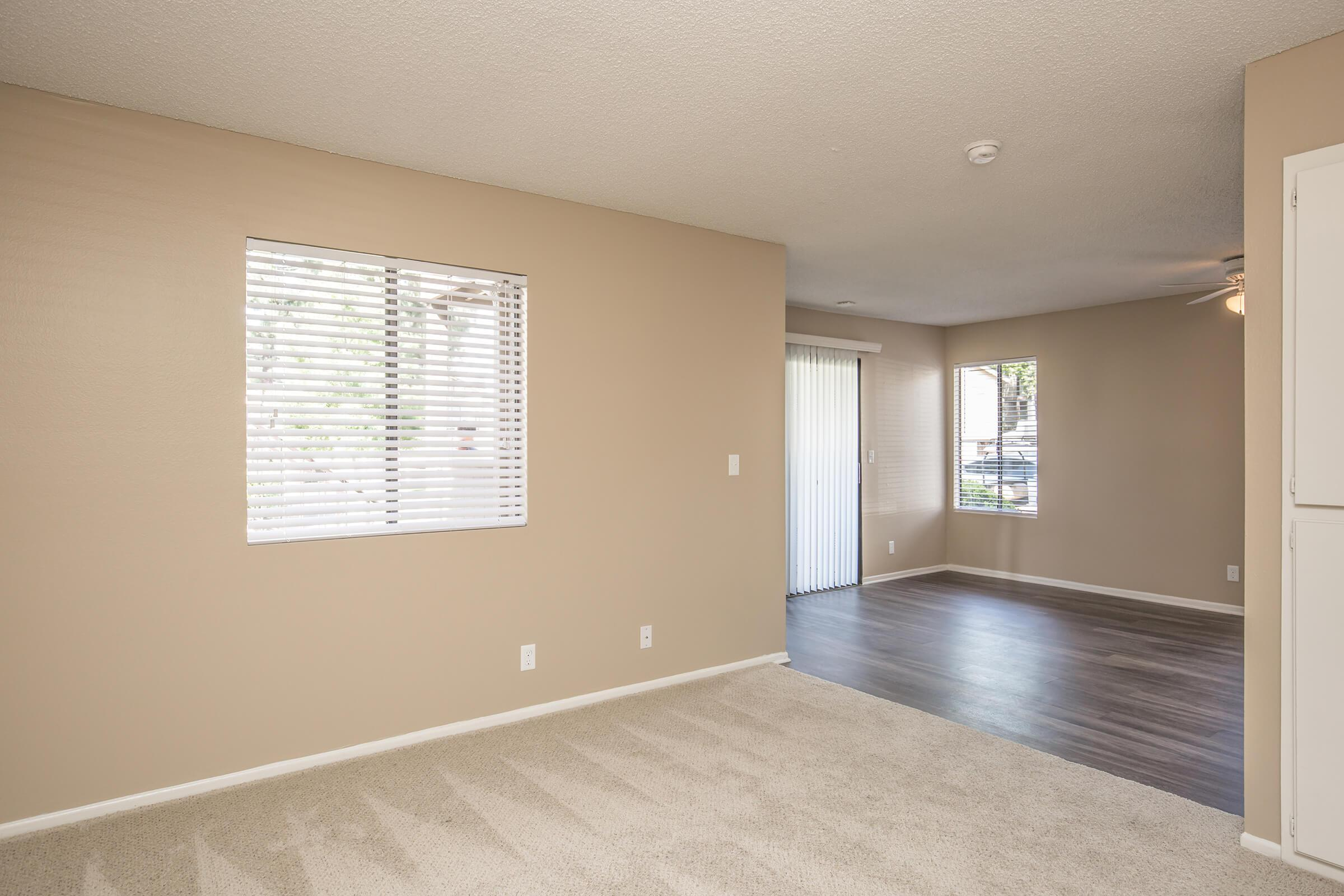 Unfurnished carpeted living room and dining room with wooden floors