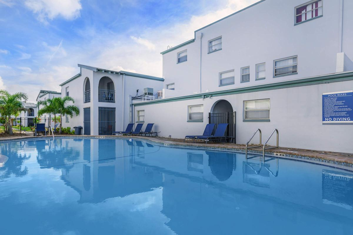 a large white building with a pool of water