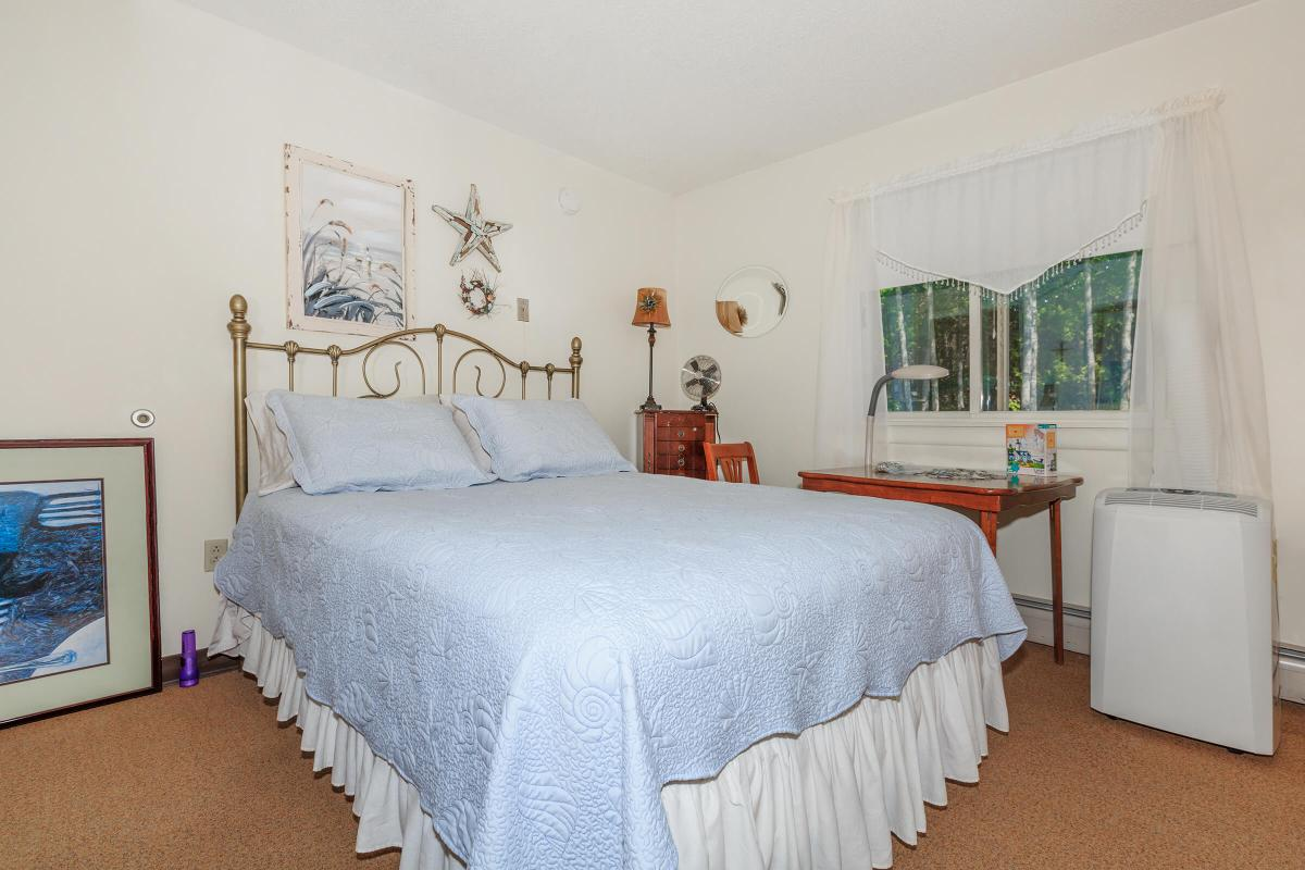 a bedroom with a bed and desk in a room