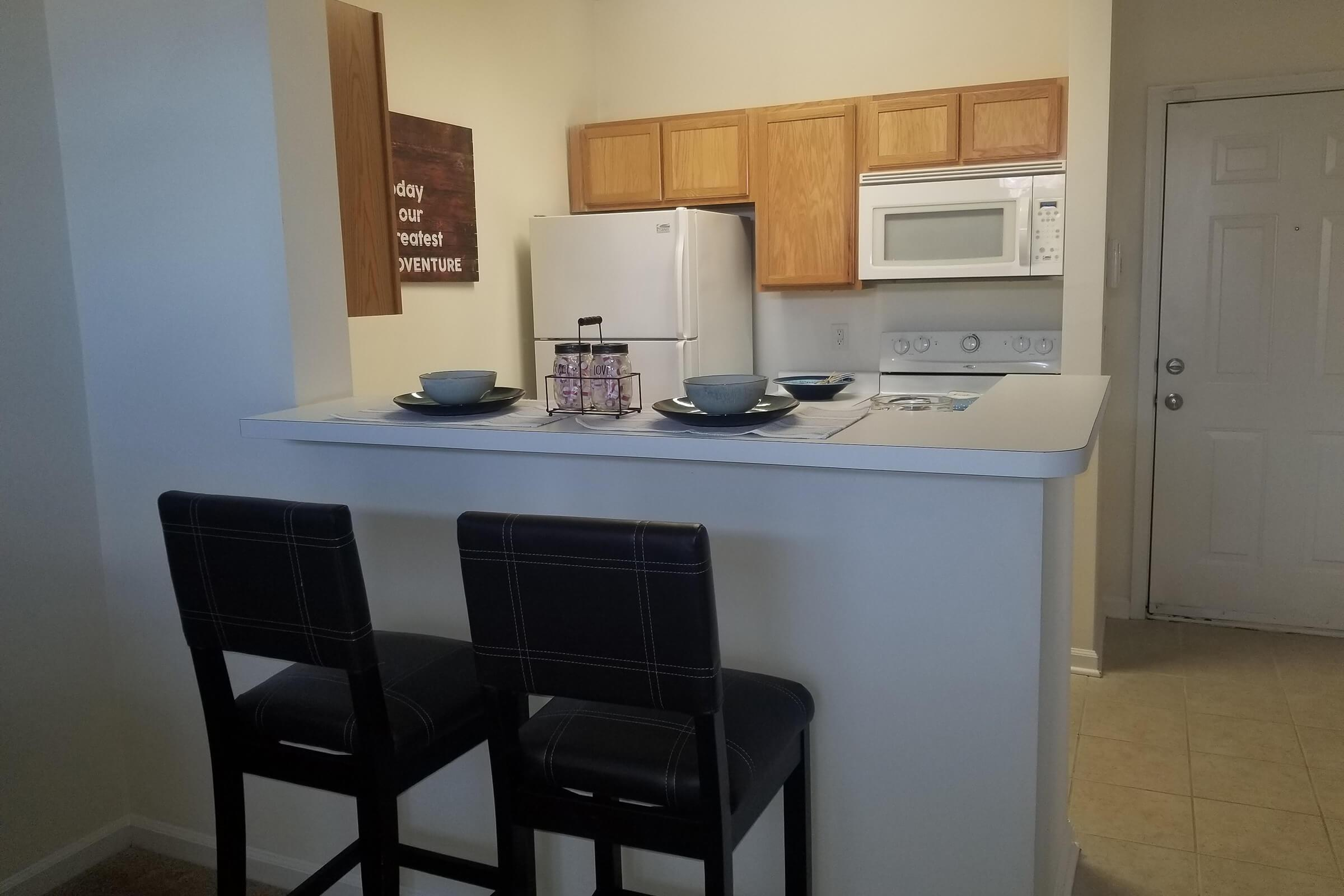 a kitchen with a white refrigerator freezer sitting in a chair
