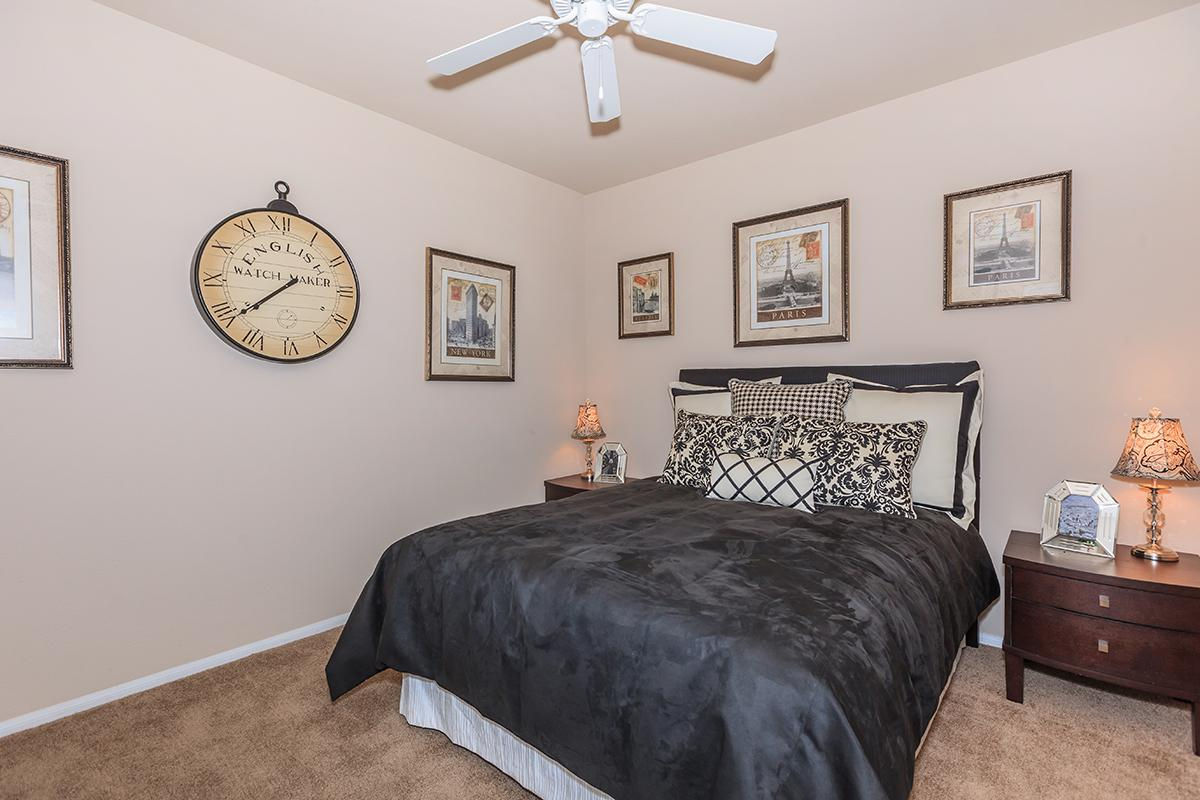 a bedroom with a clock at the top of a bed