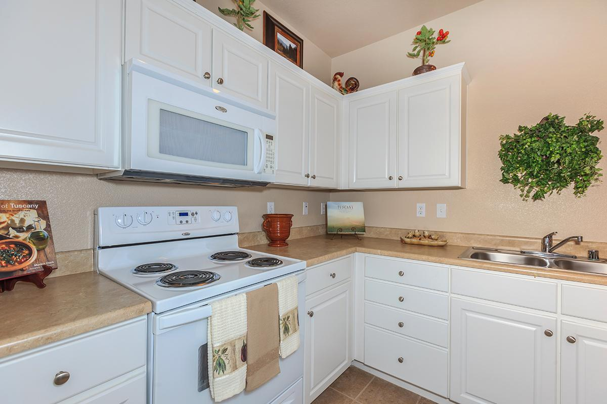 a kitchen with white cabinets and a microwave