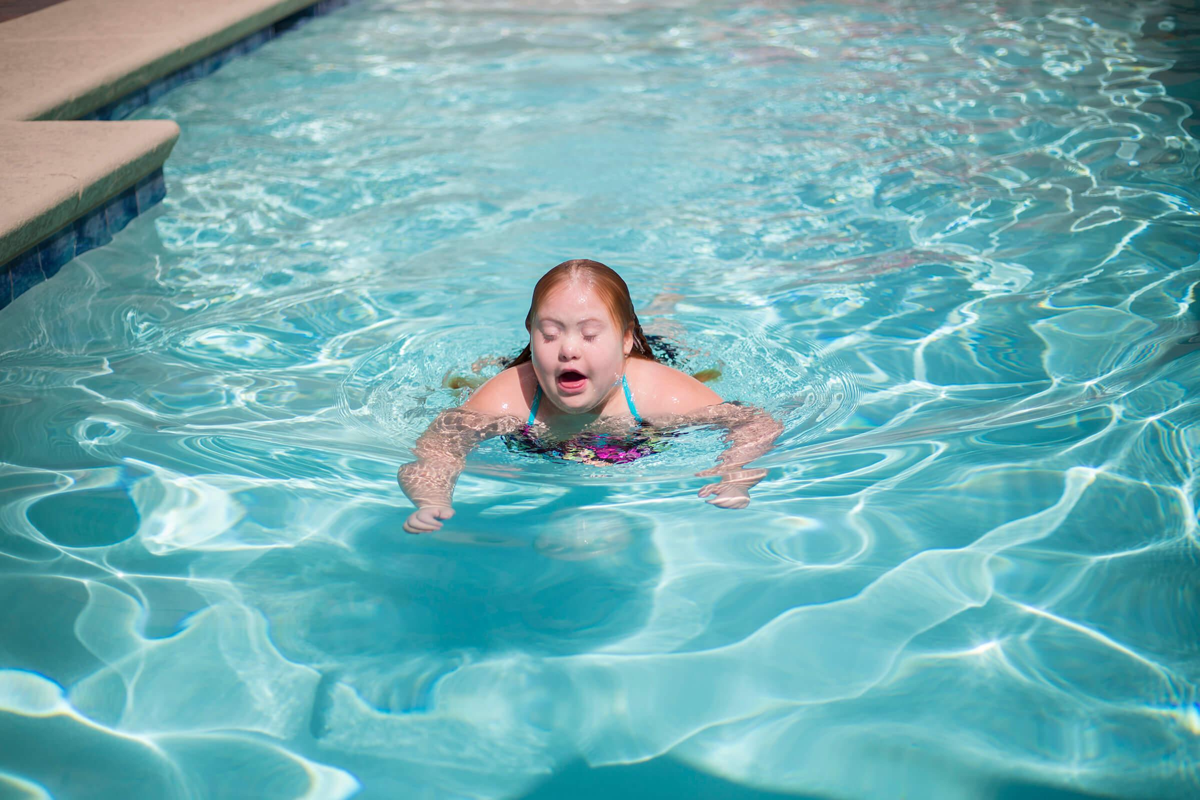 a young boy swimming in a pool of water