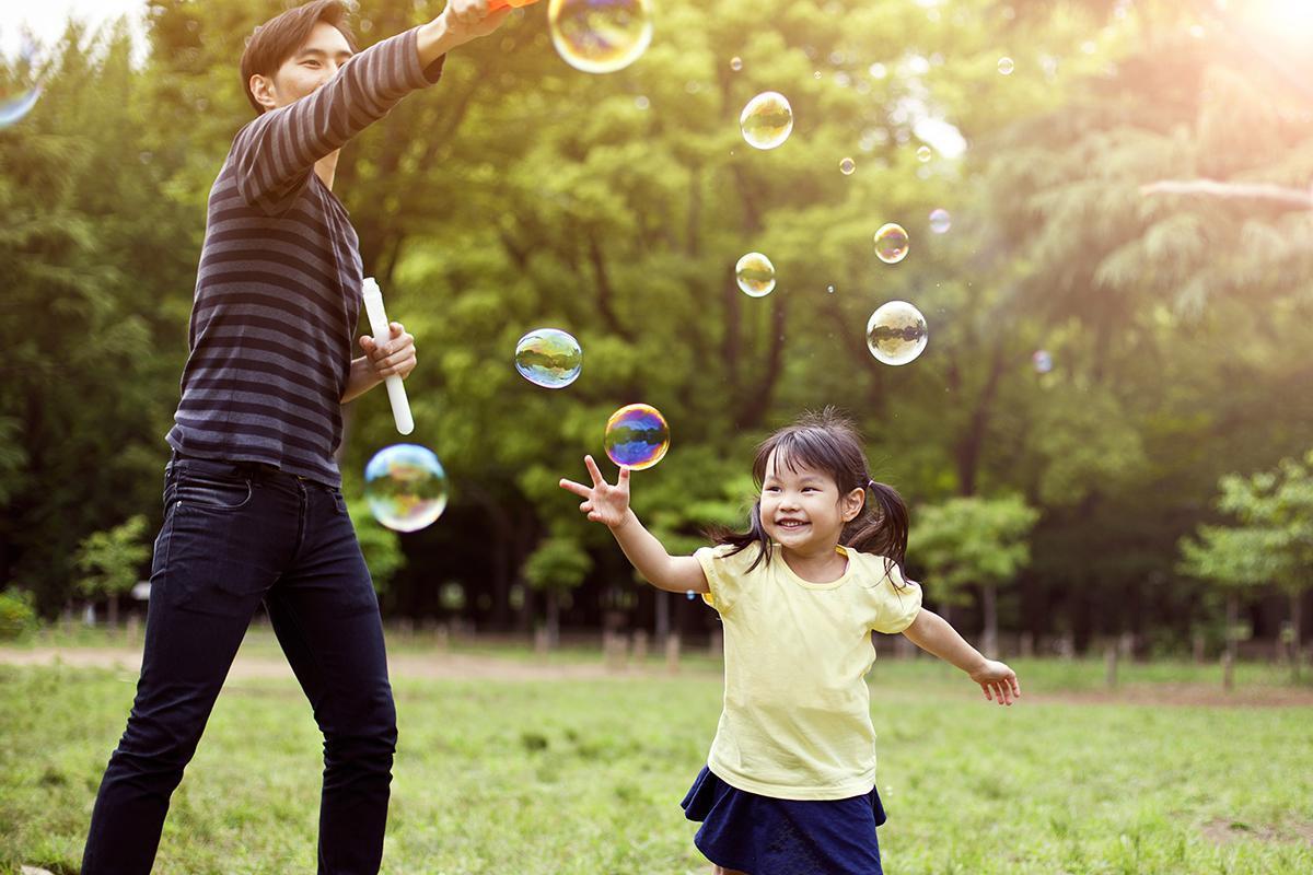 Parent & Child Having Fun Blowing Bubbles