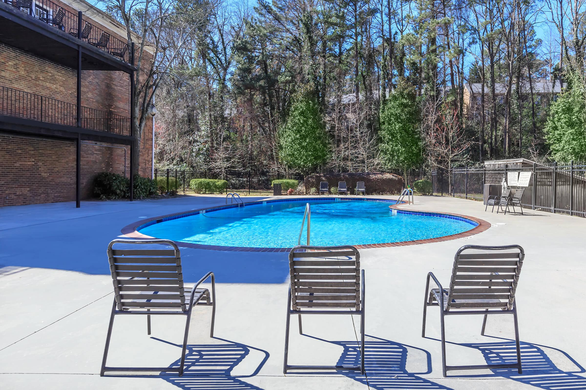 a row of lawn chairs sitting on top of a bench in a pool