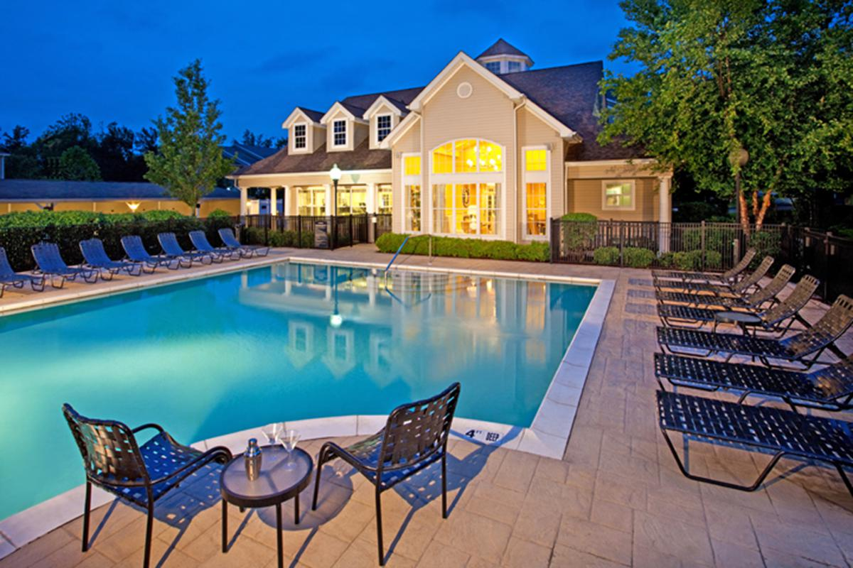 a row of lawn chairs sitting on a bench in front of a pool