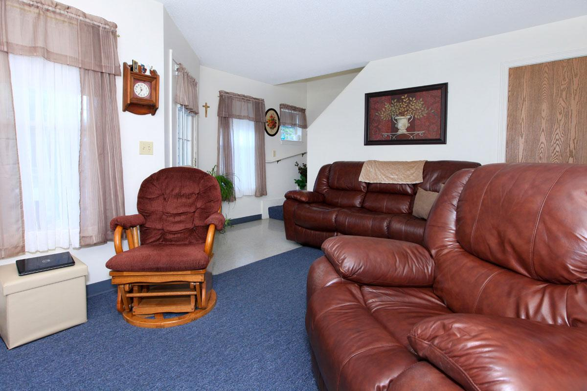 a brown leather couch in a living room filled with furniture