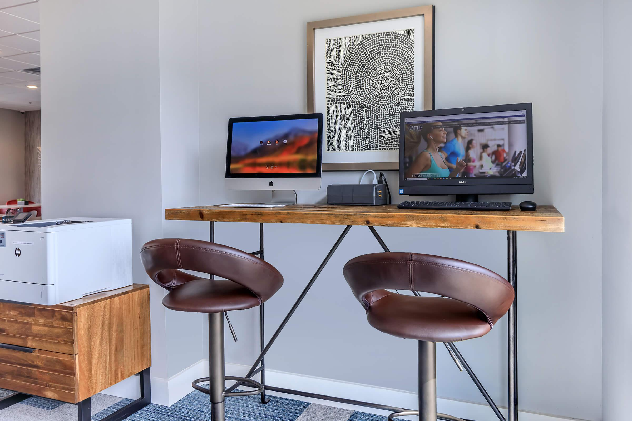 a desk with a computer and a chair in a room