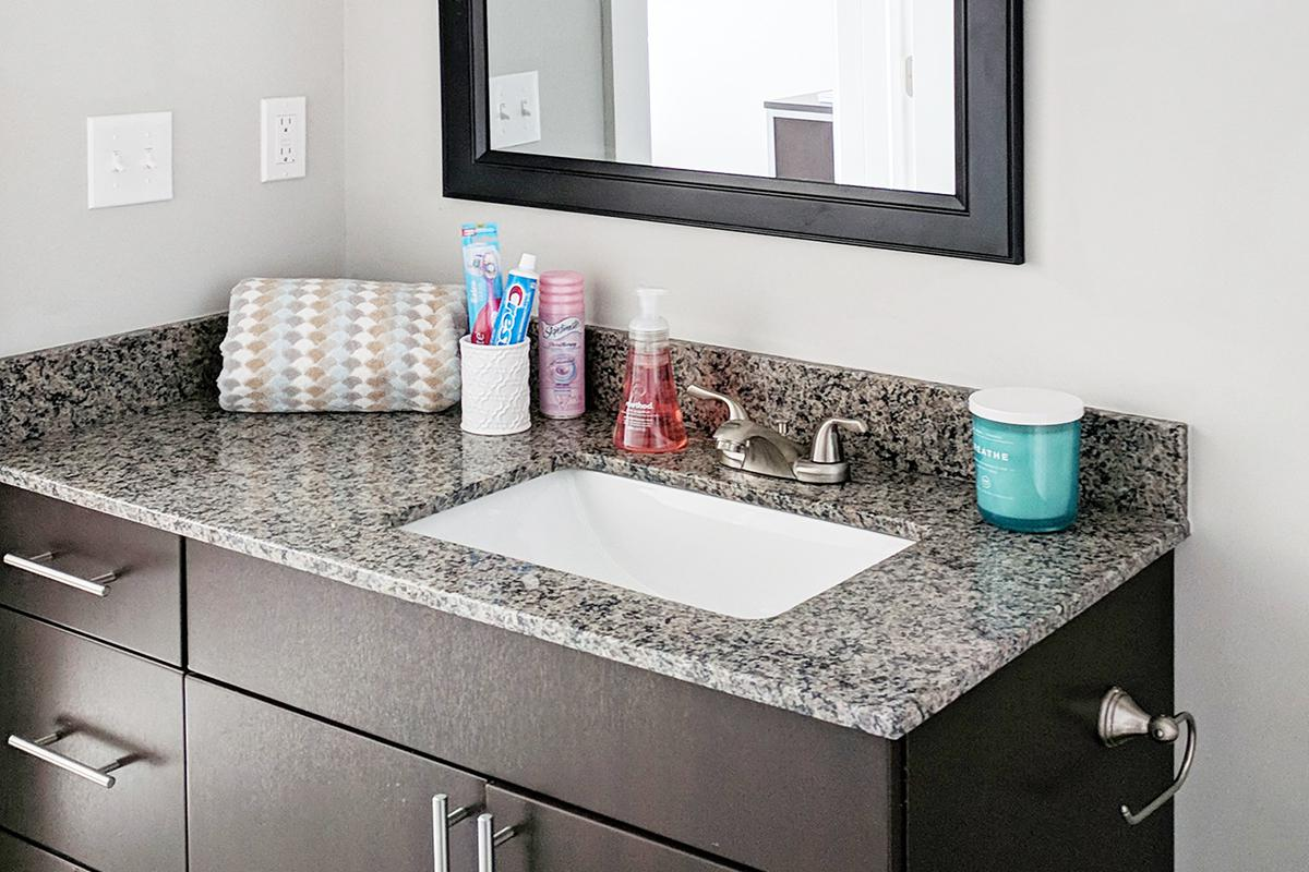 a counter with a sink and a mirror