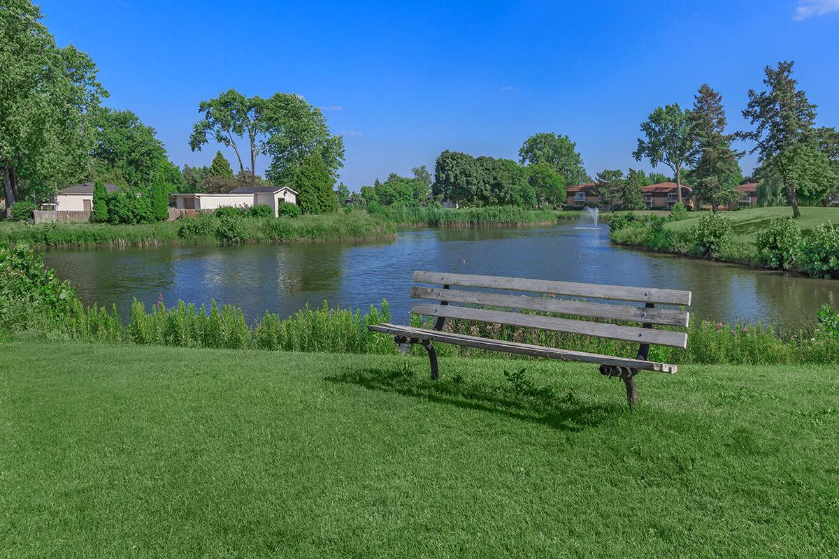 a row of park benches sitting next to a body of water