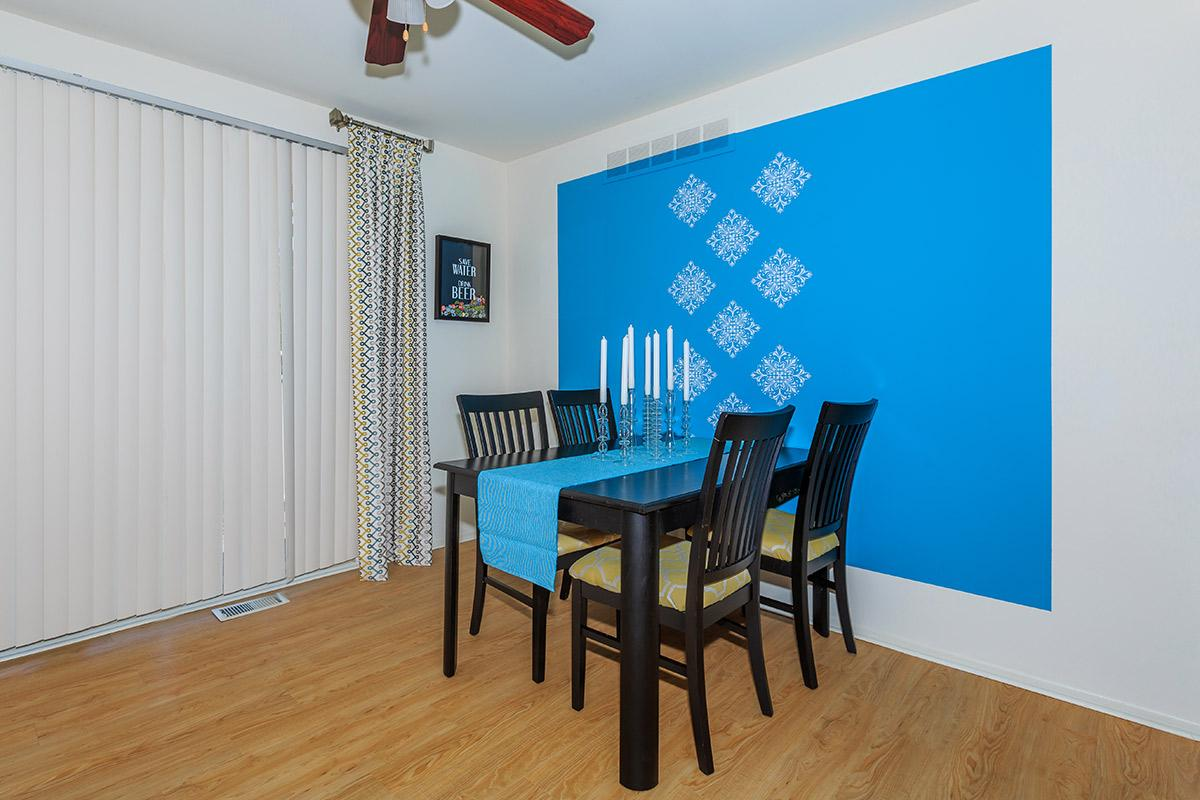 a dining room table with a blue chair