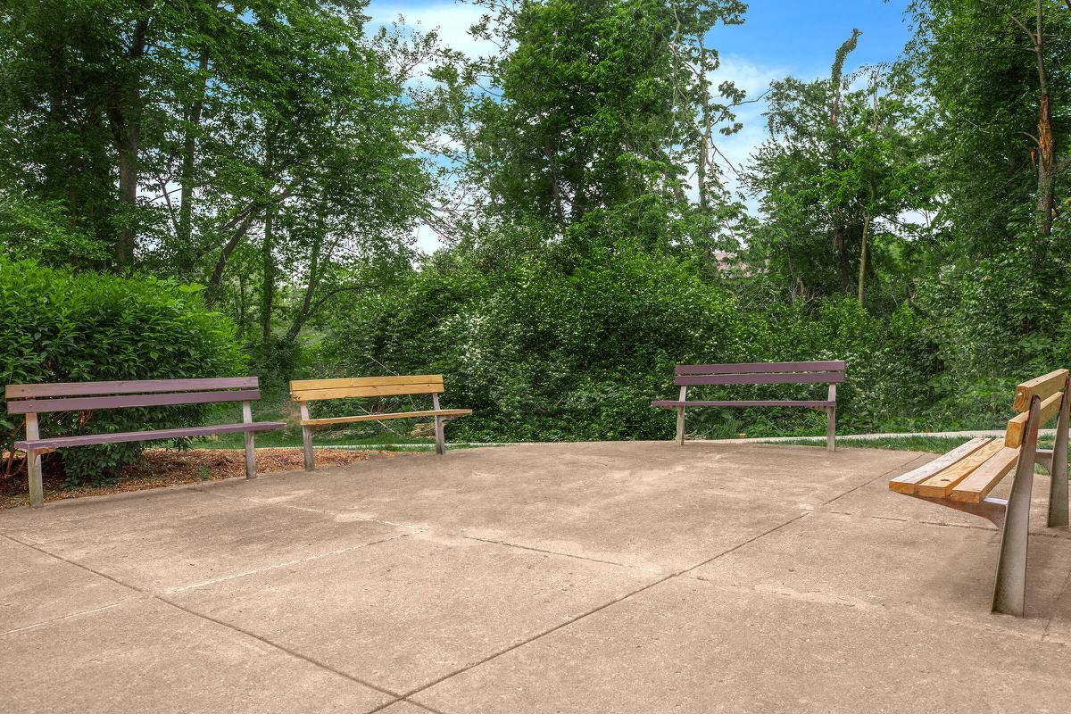 an empty park bench sitting on top of a wooden fence