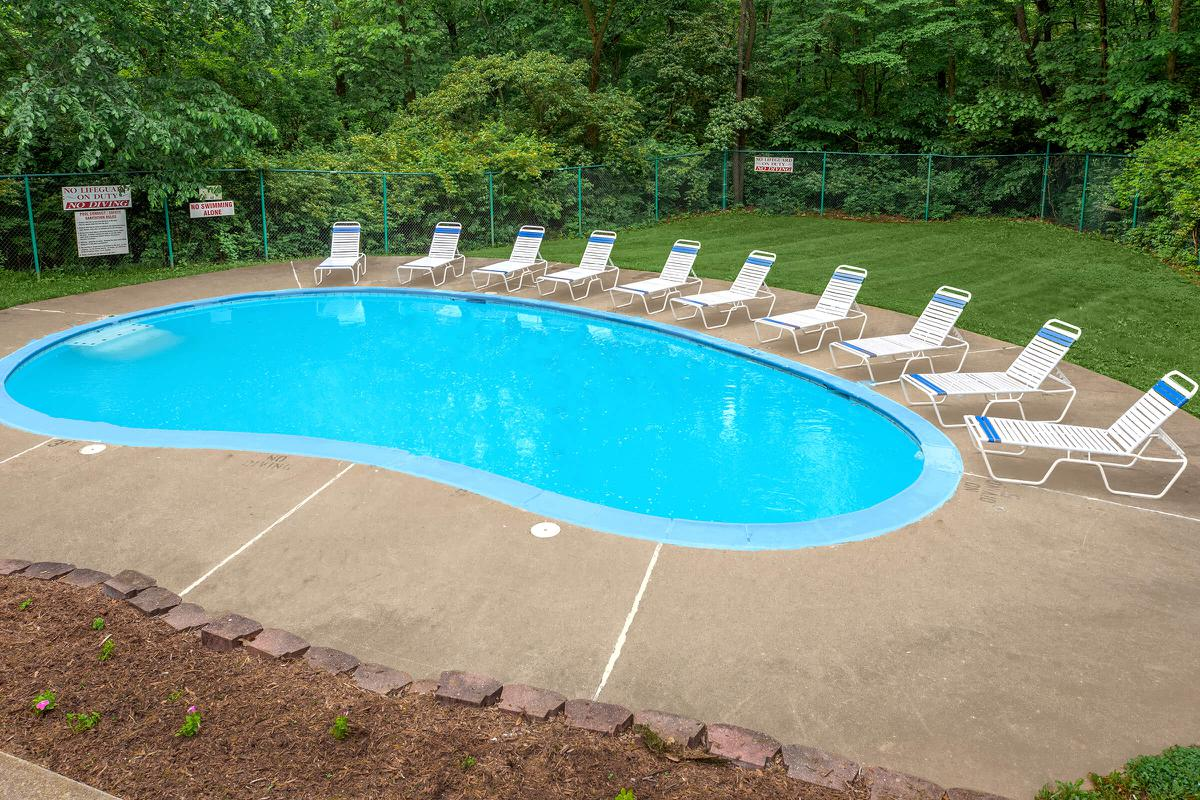 a group of lawn chairs sitting on top of a swimming pool