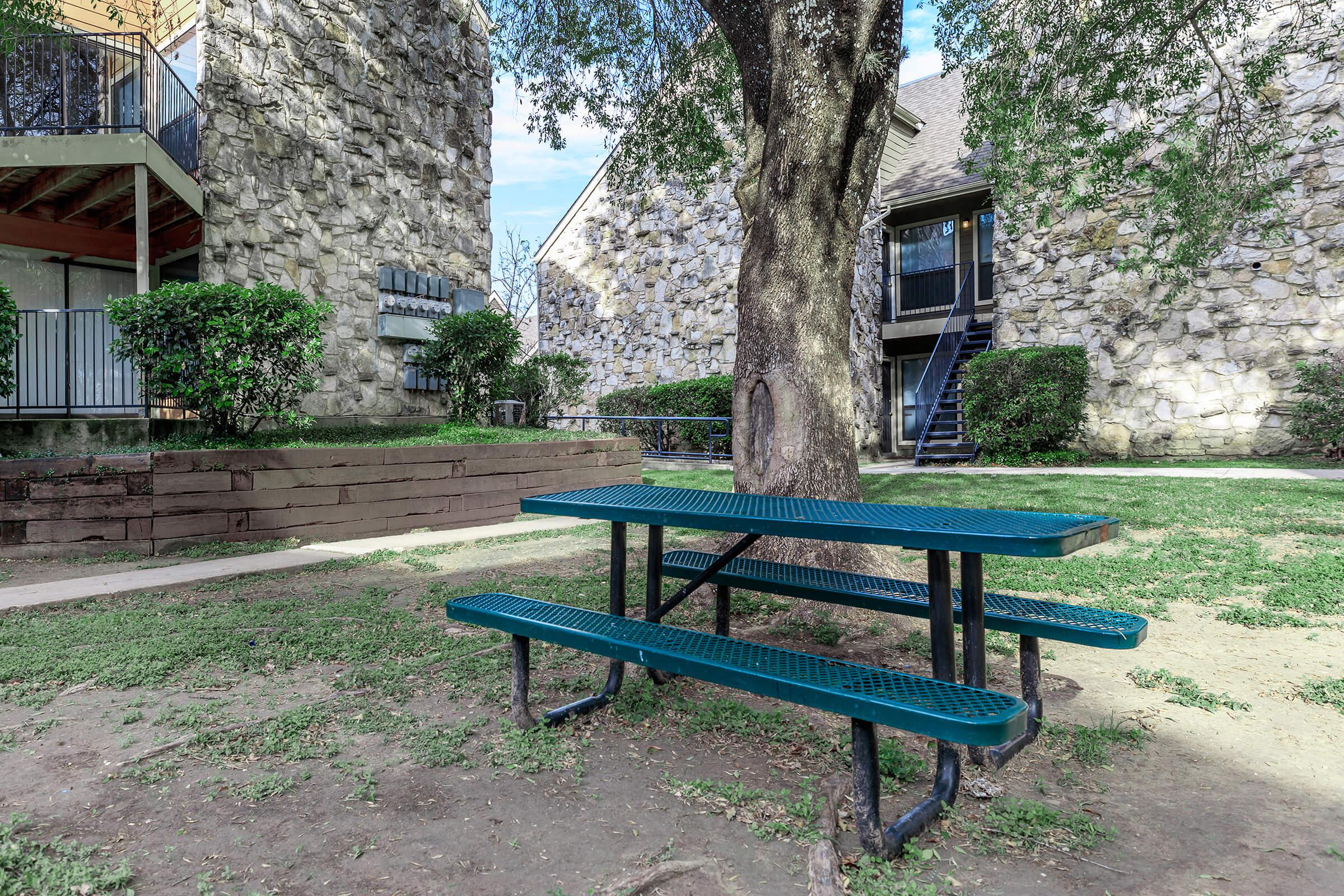 an empty park bench sitting in front of a house
