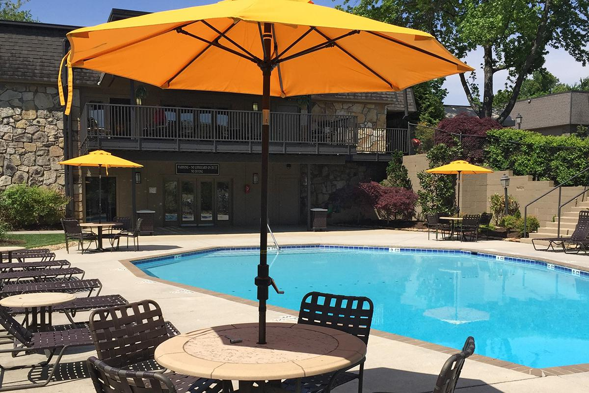 an umbrella sitting on a chair in front of a pool