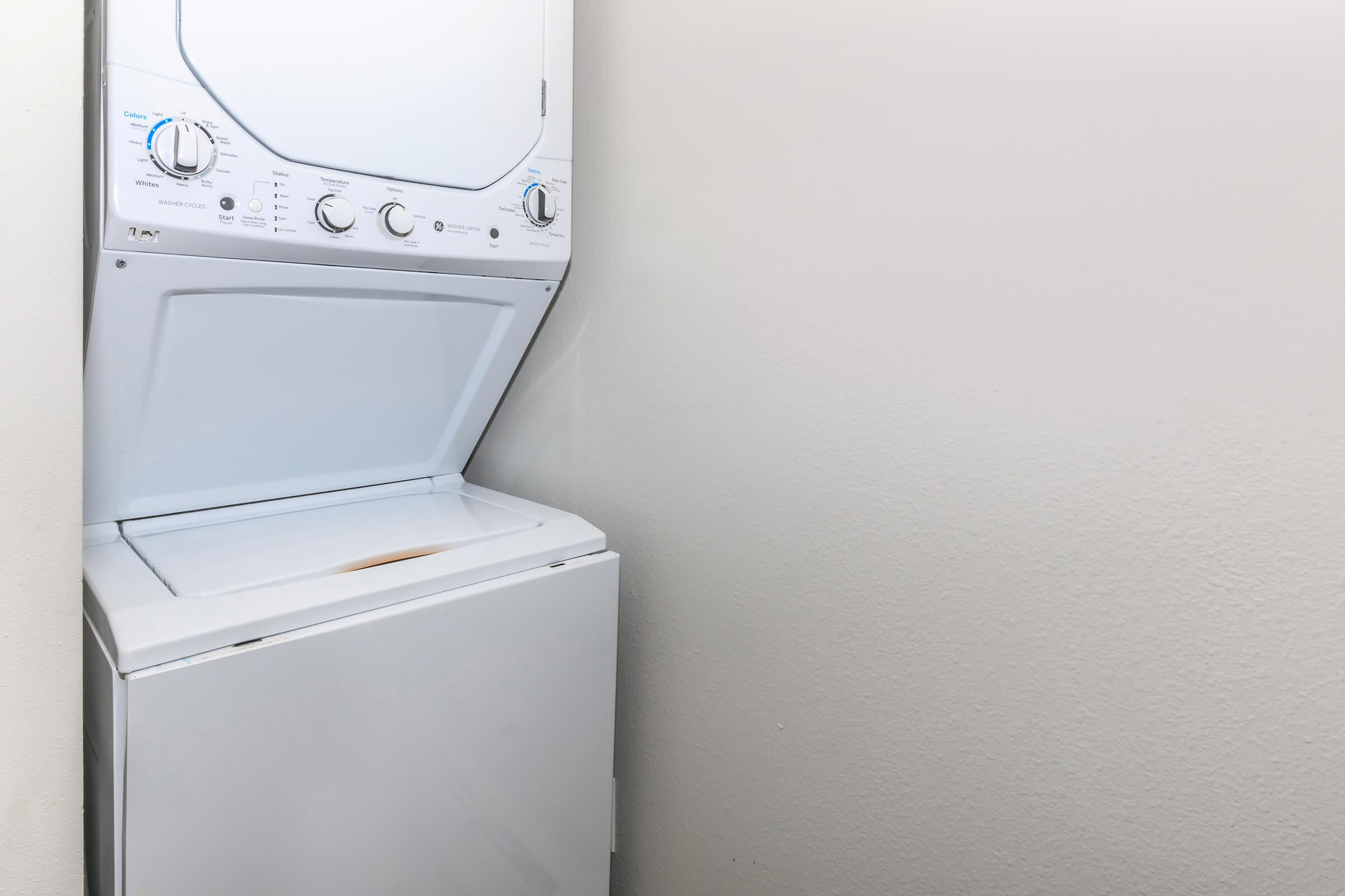 a white microwave oven sitting on top of a refrigerator