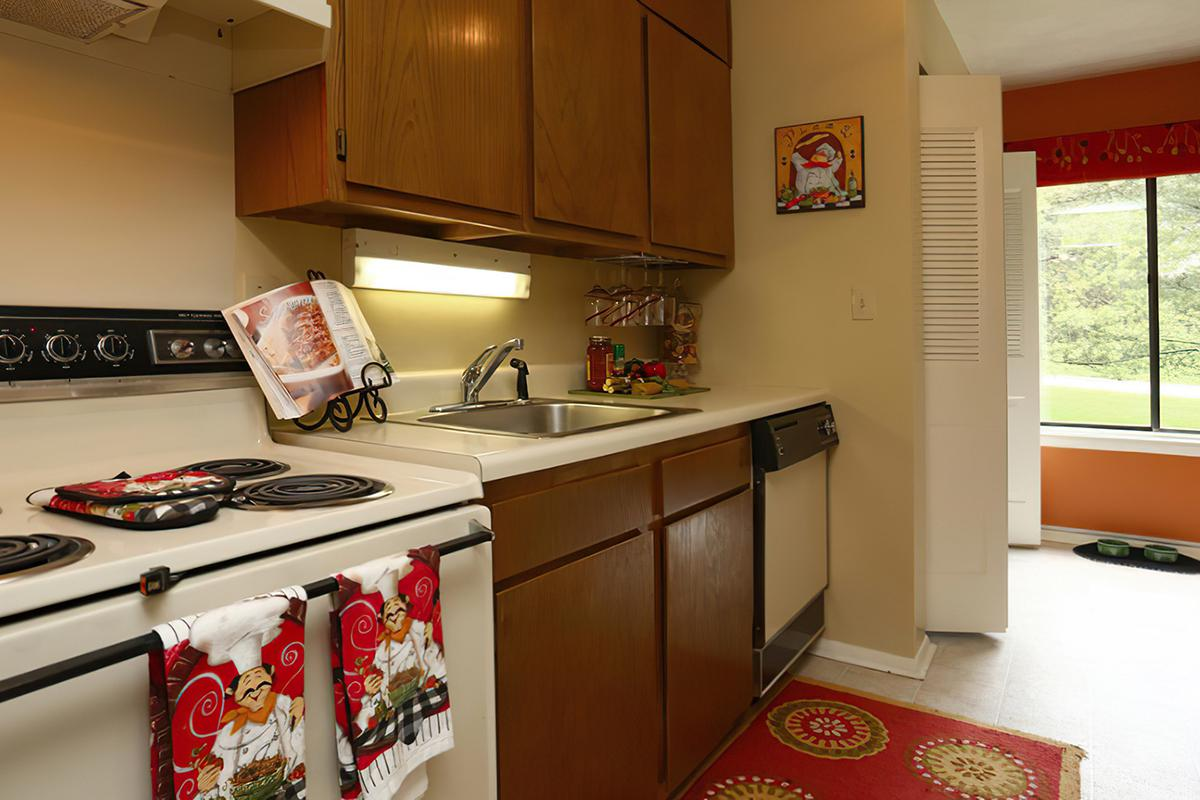 a kitchen with a stove refrigerator and table in a room