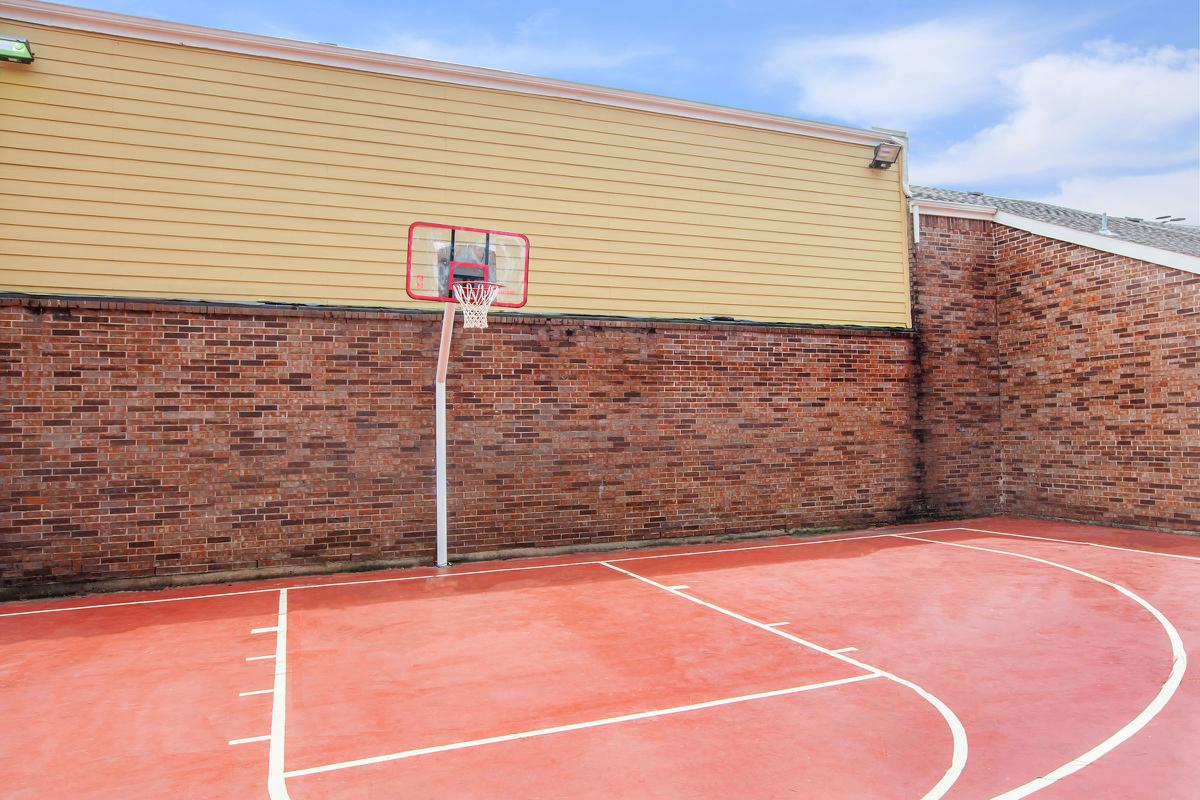 a close up of a red brick building with a racket on a court