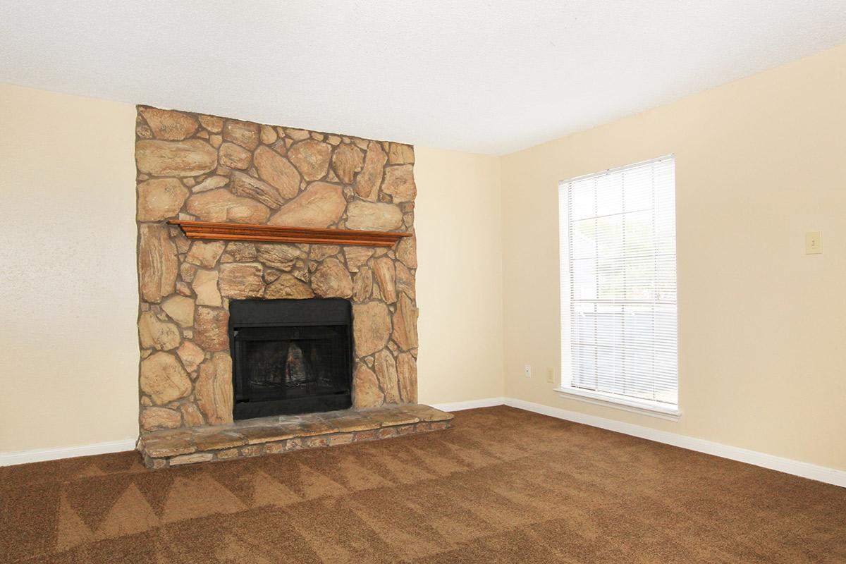 a living room with a stone fireplace