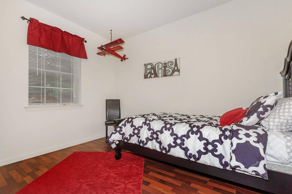 a bedroom with a red rug