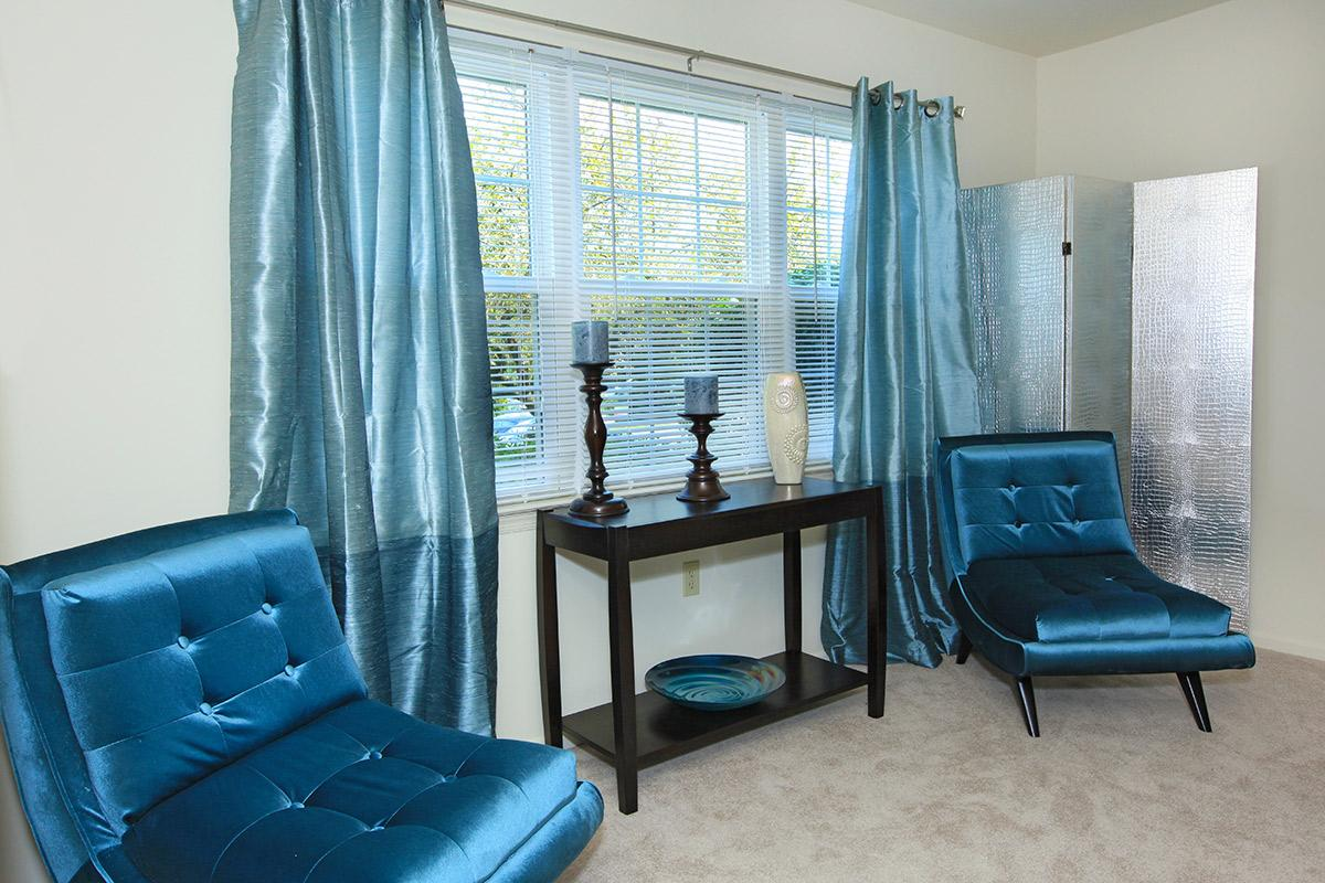 a bedroom with a blue chair in a room