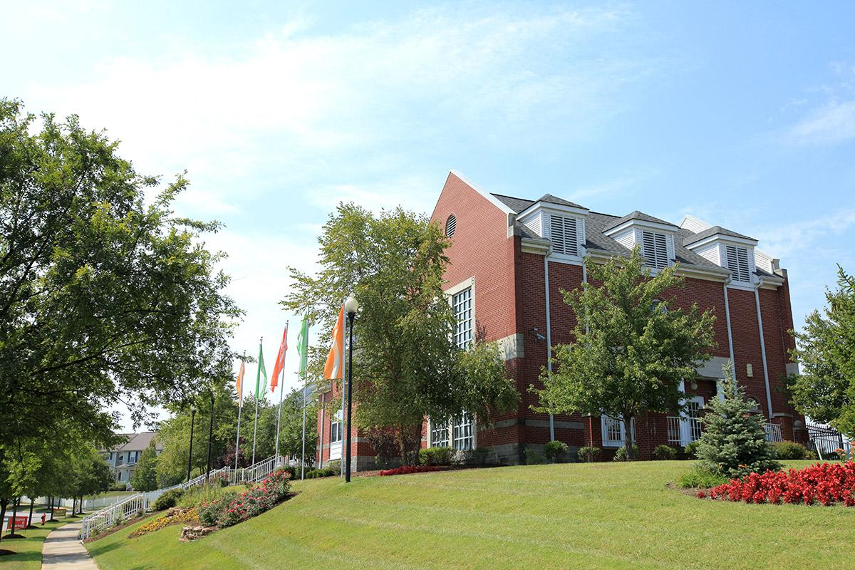 a large brick building with grass and trees