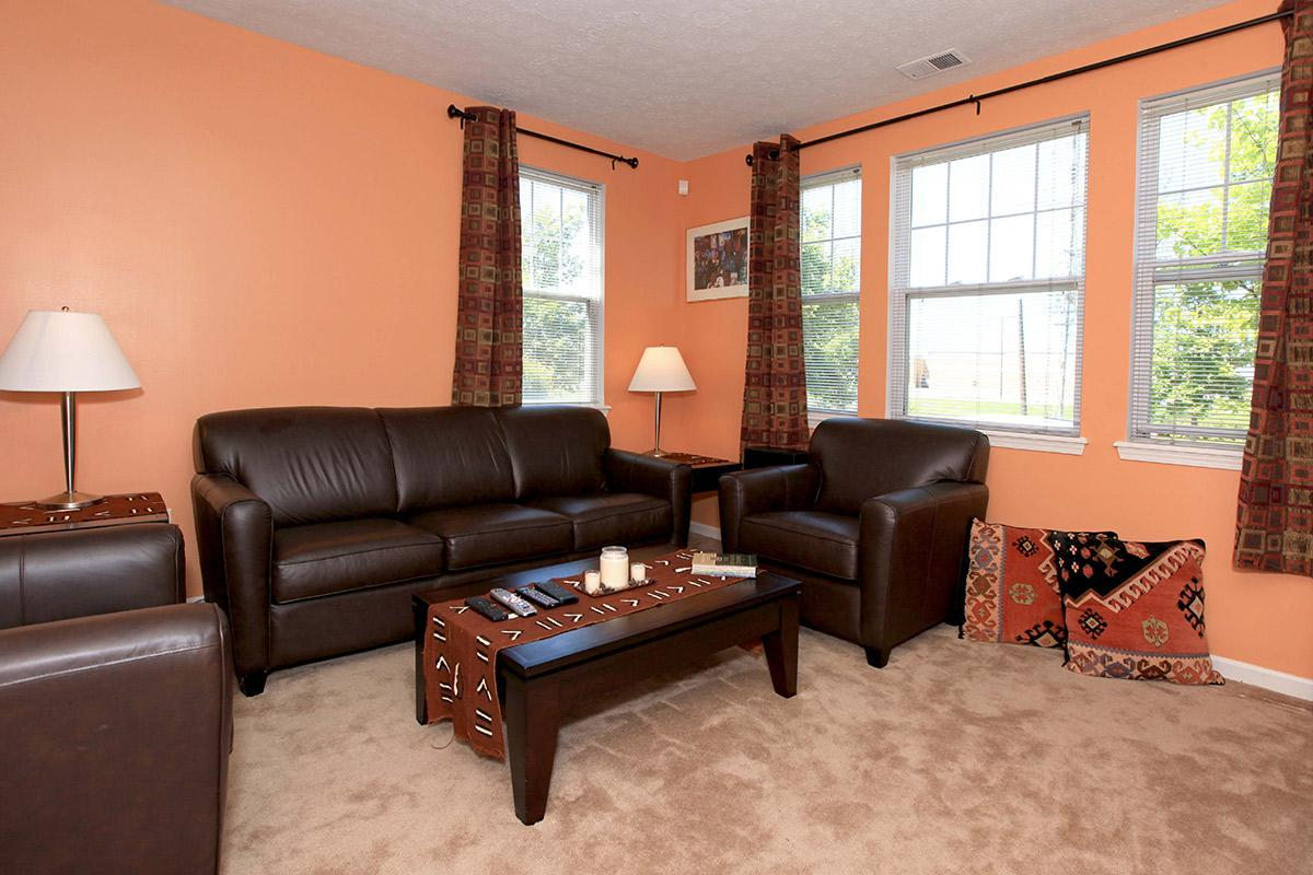 a brown leather couch in a living room filled with furniture and a window