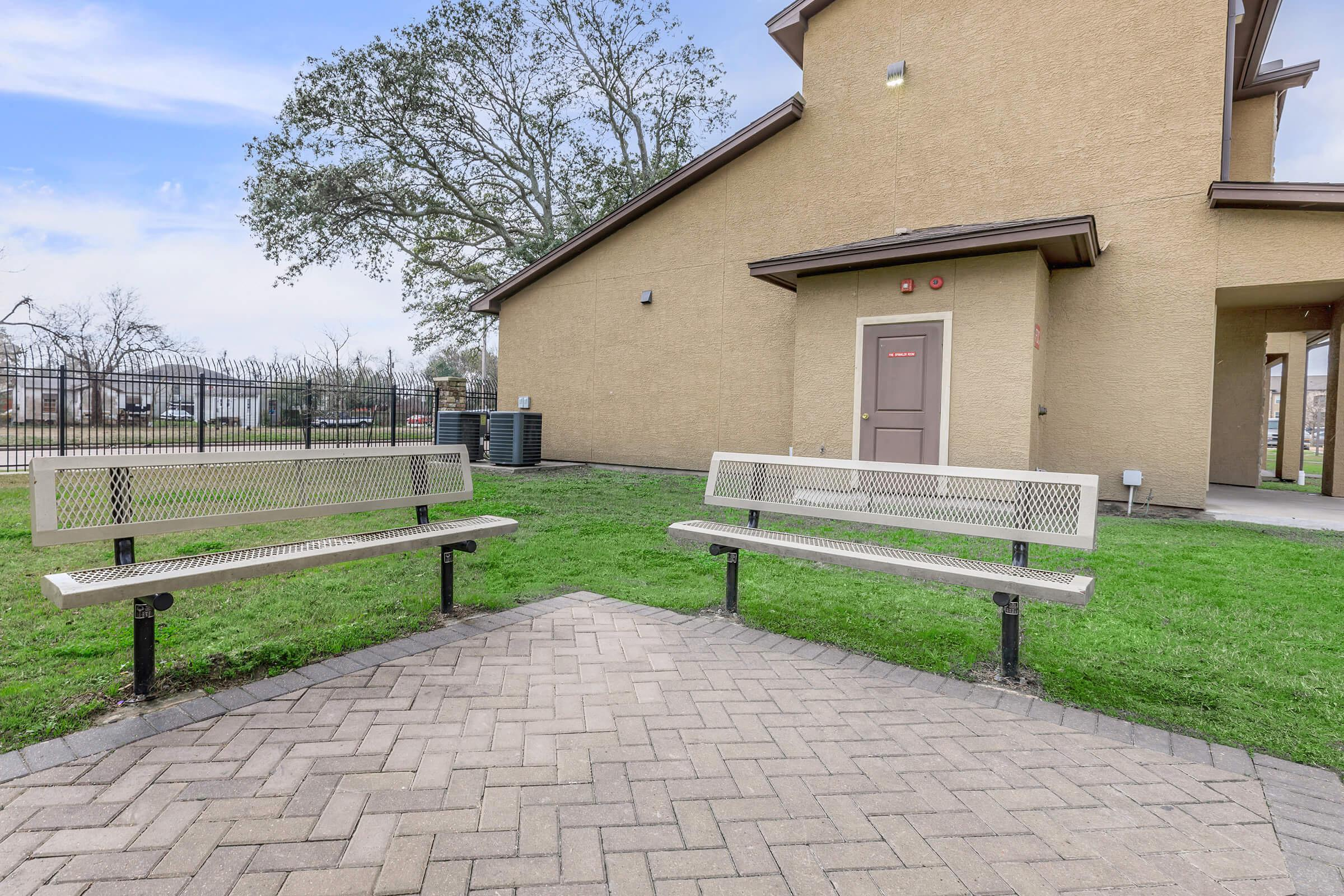 a bench in front of a brick building