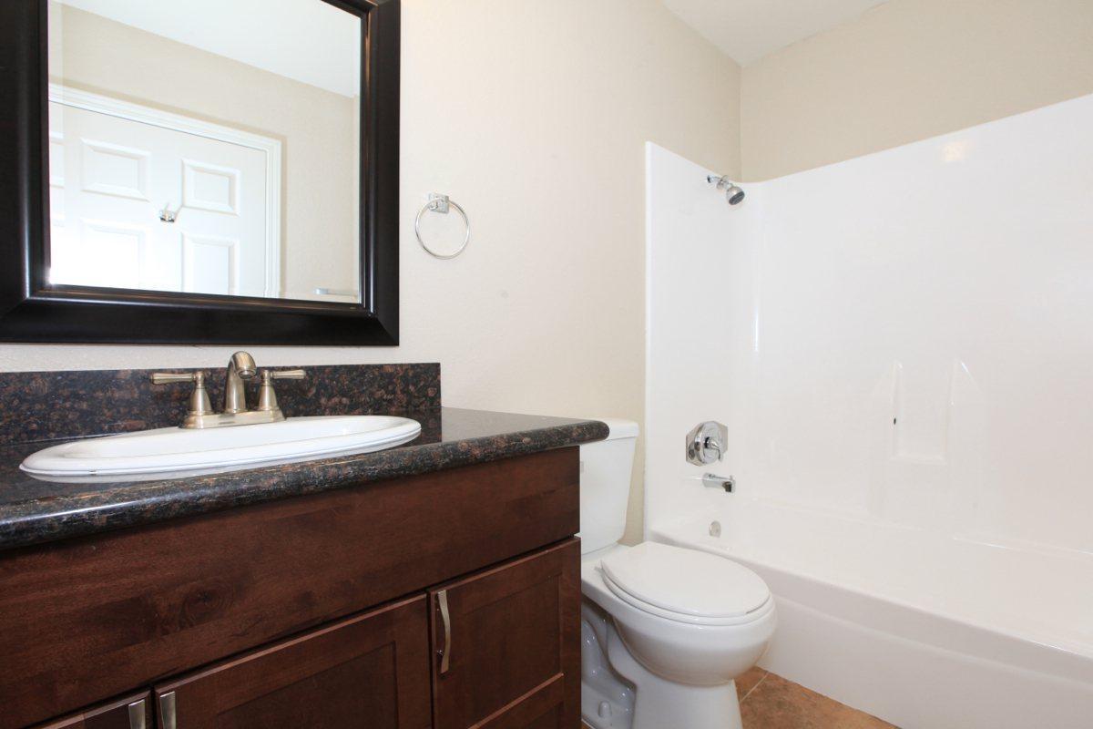 a white sink sitting under a mirror