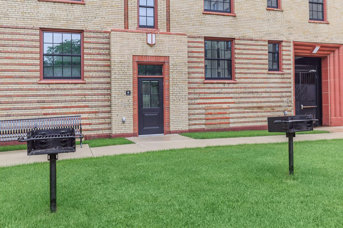 a large lawn in front of a brick building