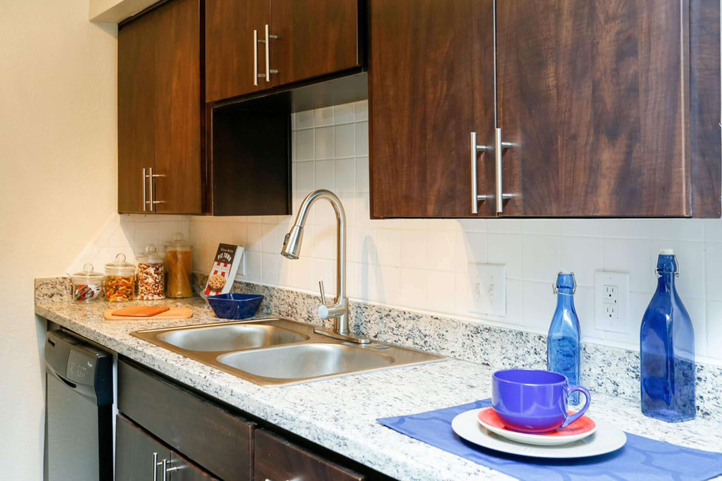 a kitchen with a sink and a bottle on the counter