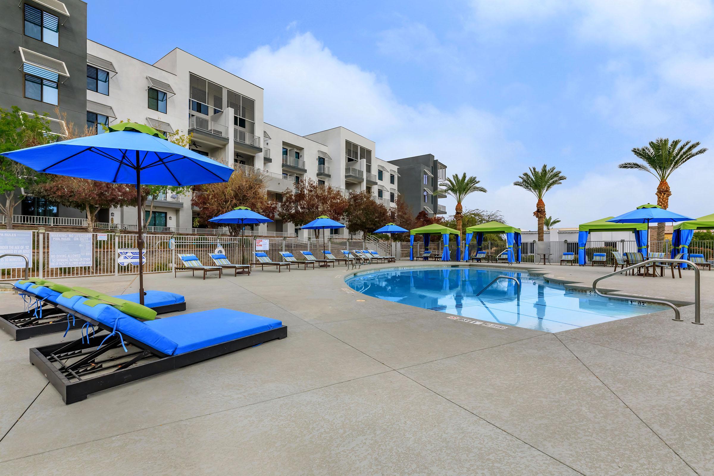 a blue umbrella sitting next to a pool